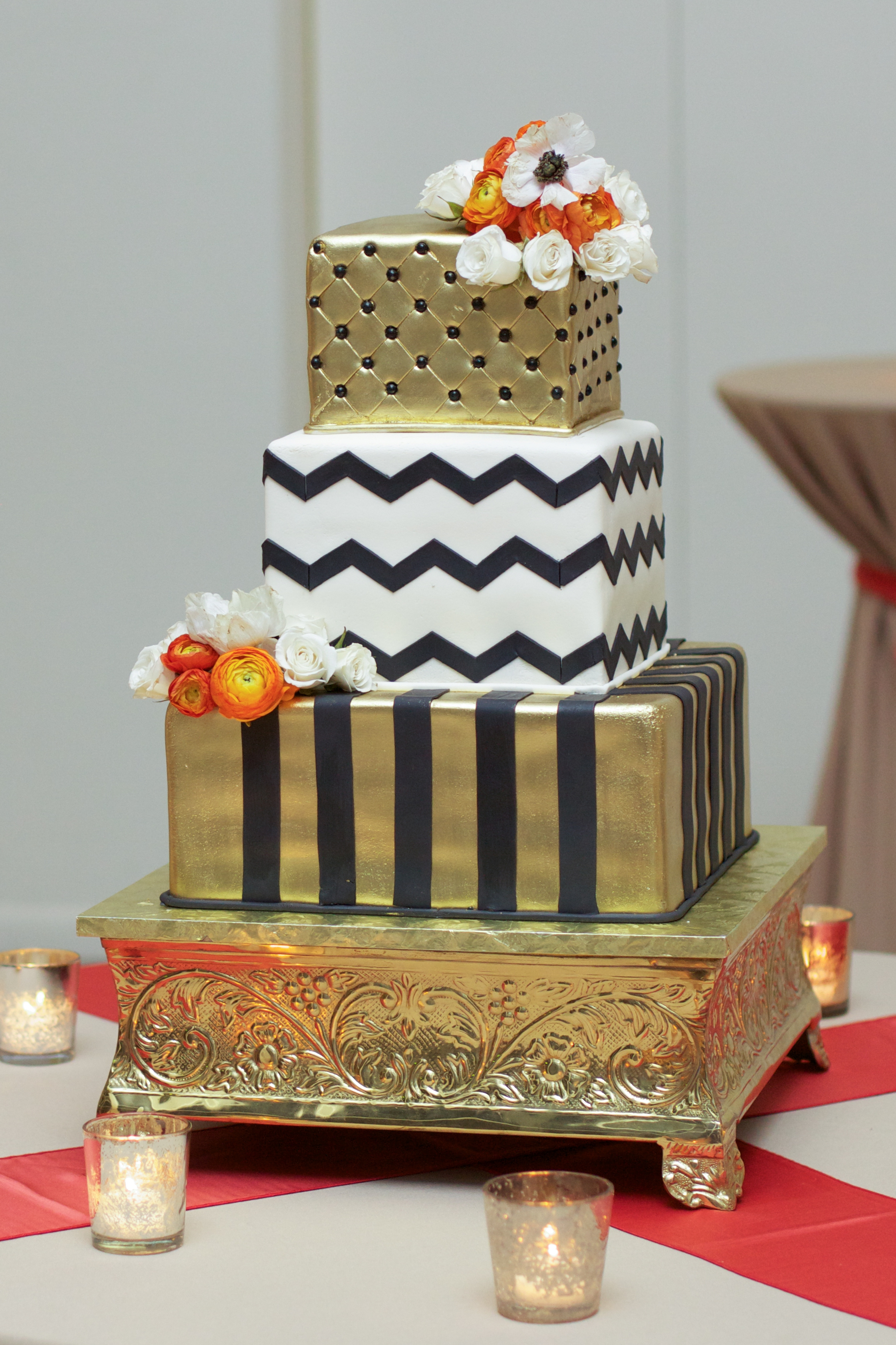 The wedding cake design incorporated black, white, and gold leaf with clusters of fresh flowers