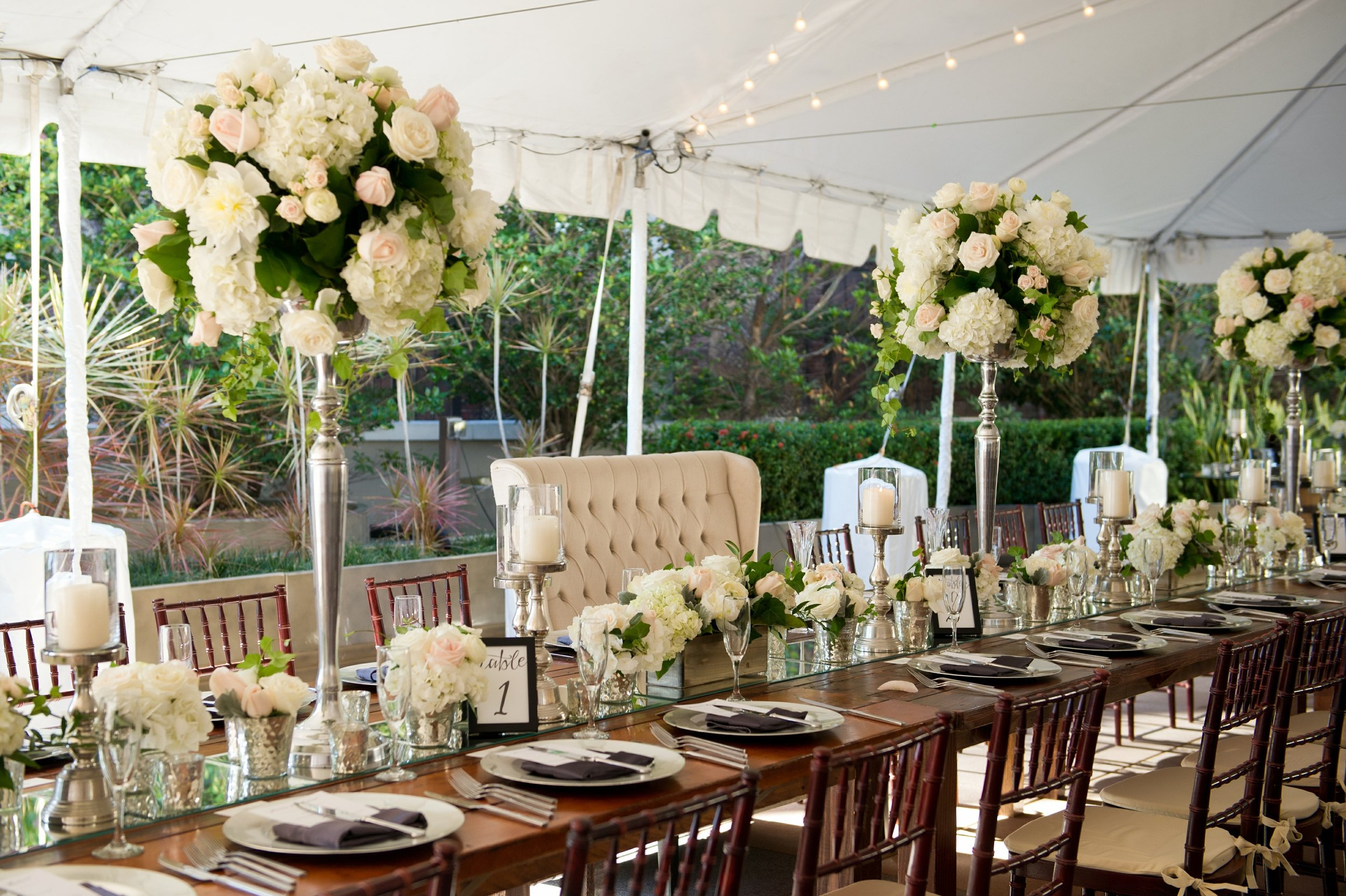 Mirrored table runners boasted silver candlesticks and wood hedge boxes of bountiful flora, with towering loose arrangements accenting the head table and a plush tufted loveseat for the bride and groom.