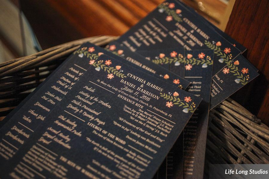 Even the custom wedding programs reflected the peach and pink flora in the design