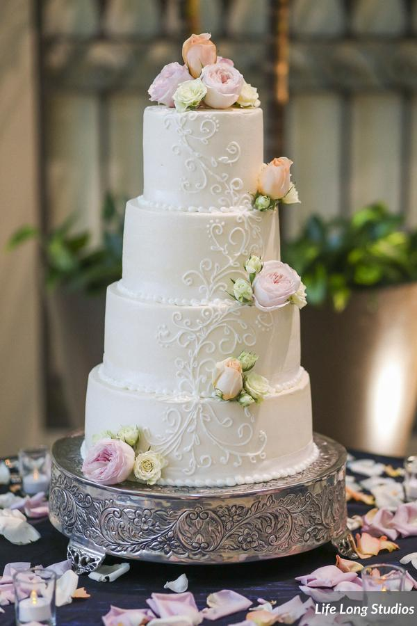 The buttercream wedding cake featured a delicate piped detail and fresh rose accents