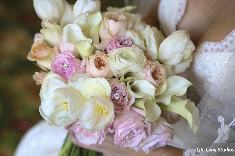 The bride's bouquet featured white tulips, roses, &calla lilies, accented with blush &peach roses.