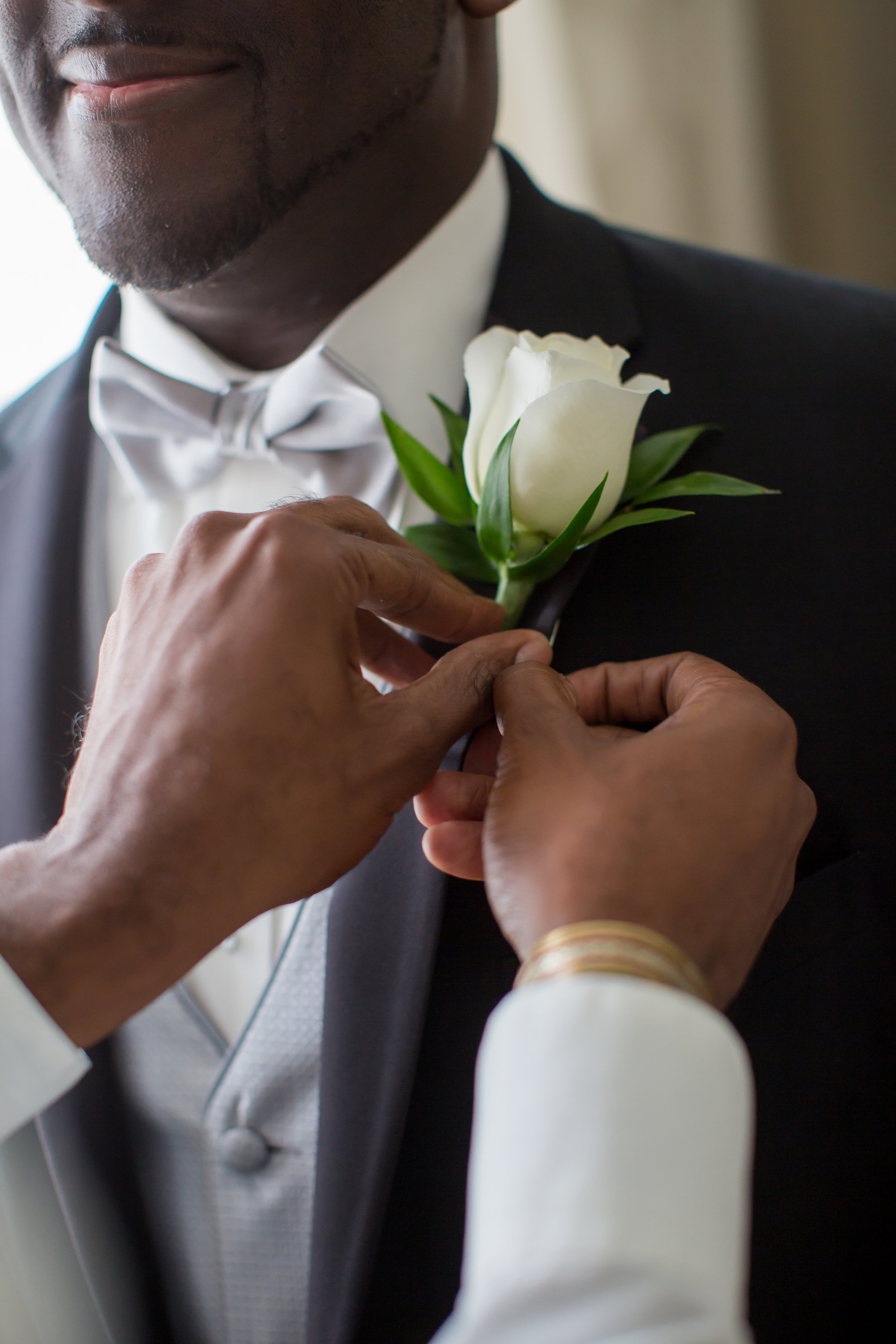 A simple white rose boutonniere was accented with sprigs of greenery