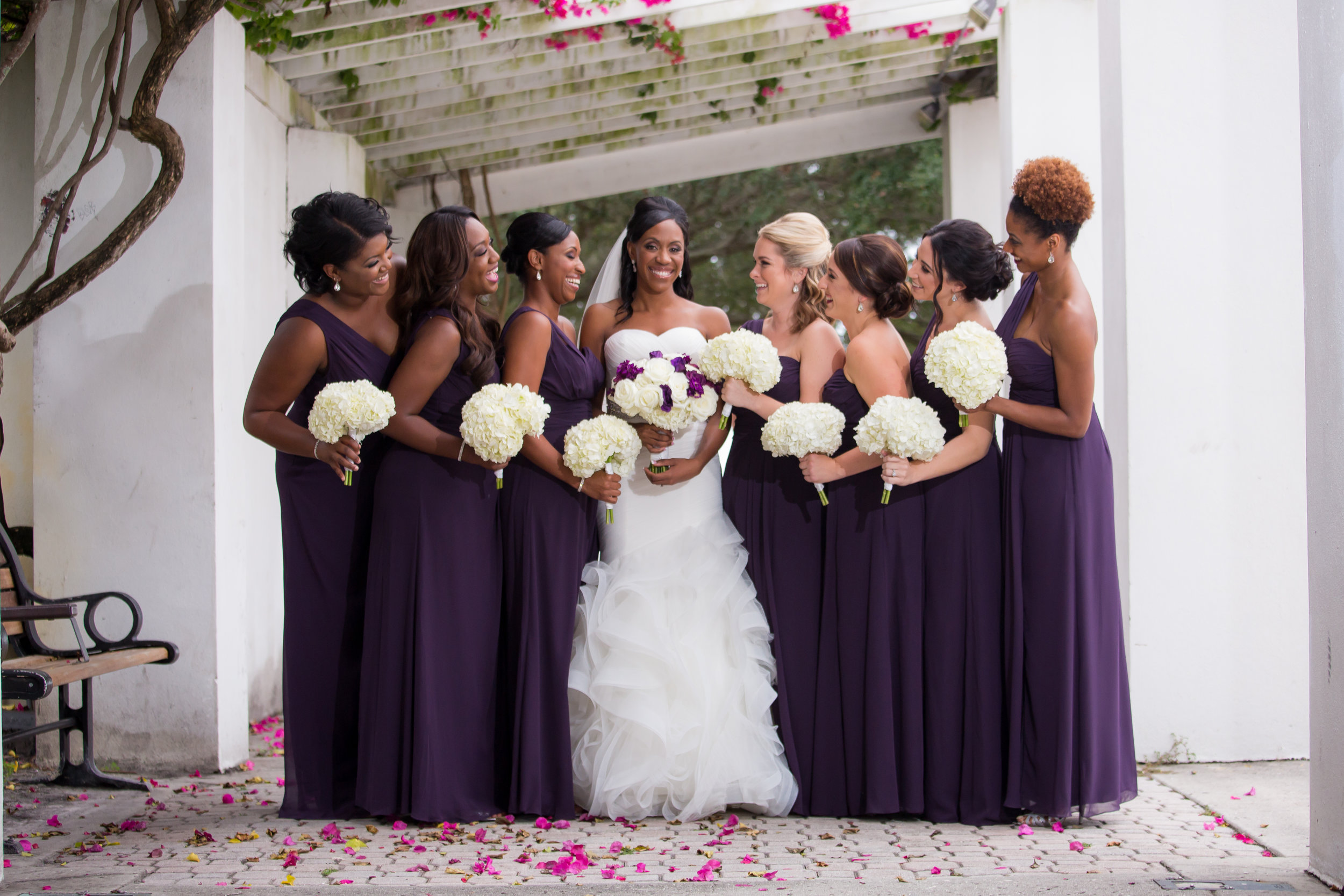 The bride looked stunning in her mermaid gown with rhinestone belt, flanked by her friends and bridesmaids in chic eggplant dresses.