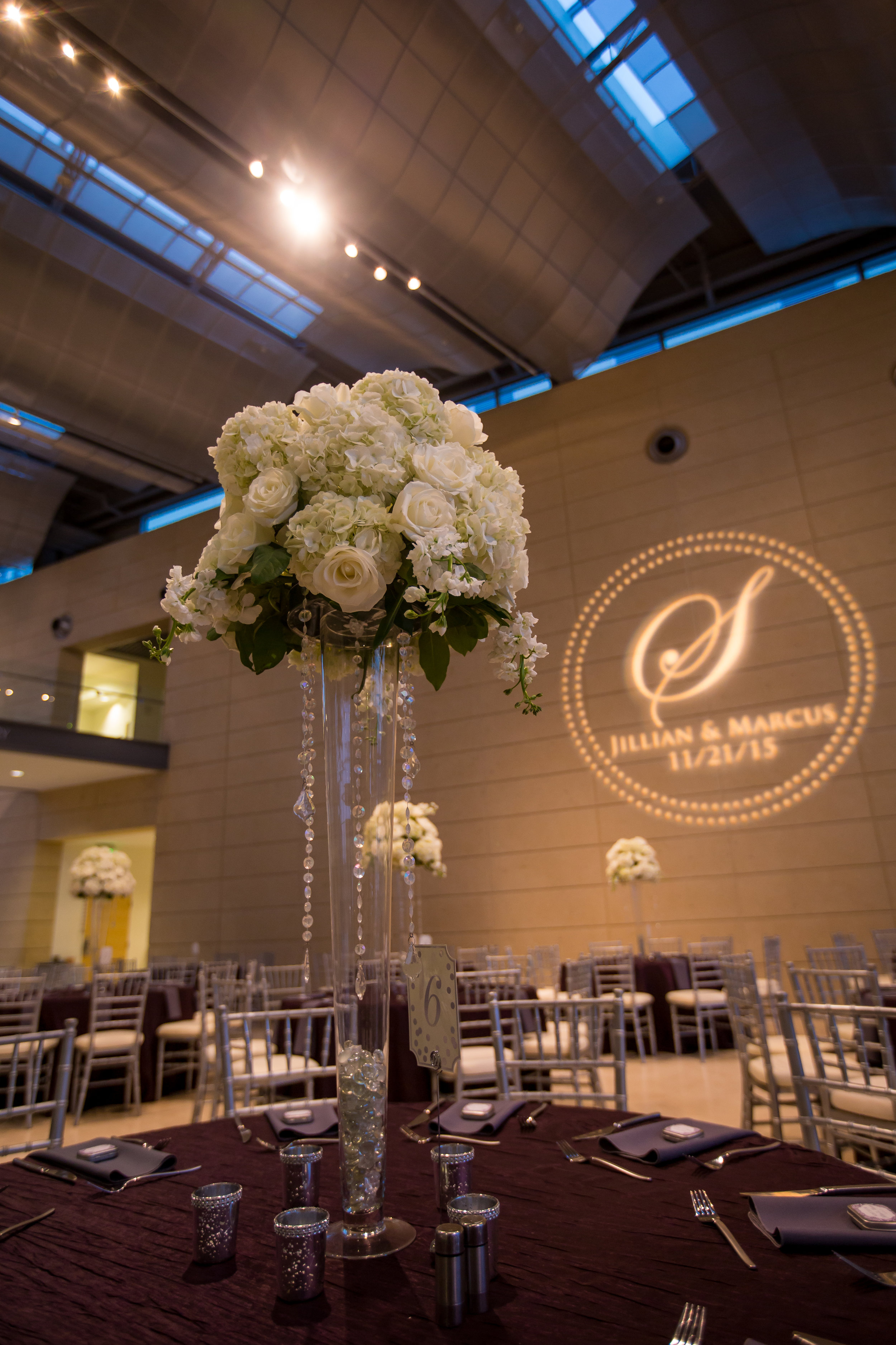 Classic white flowers with striking purple accents with sparkling crystals and candlelight elevated the ceremony and reception decor.
