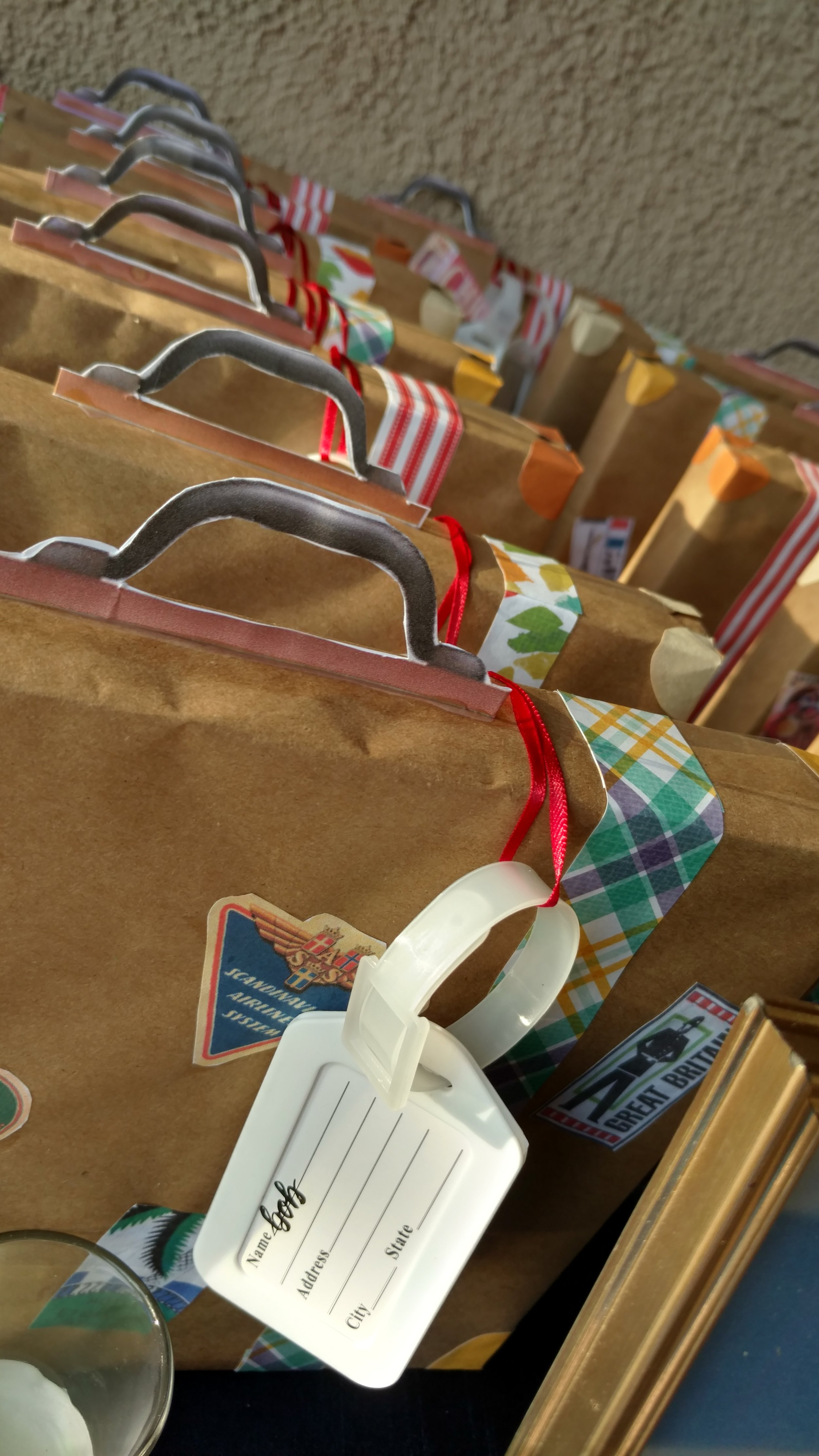Use cardstock to decorate each box with colorful suitcase straps and corners.