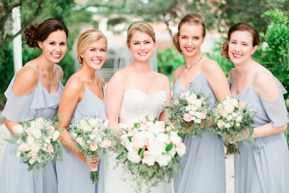 Bridesmaids donned blue-grey chiffon gowns with ruffle details.