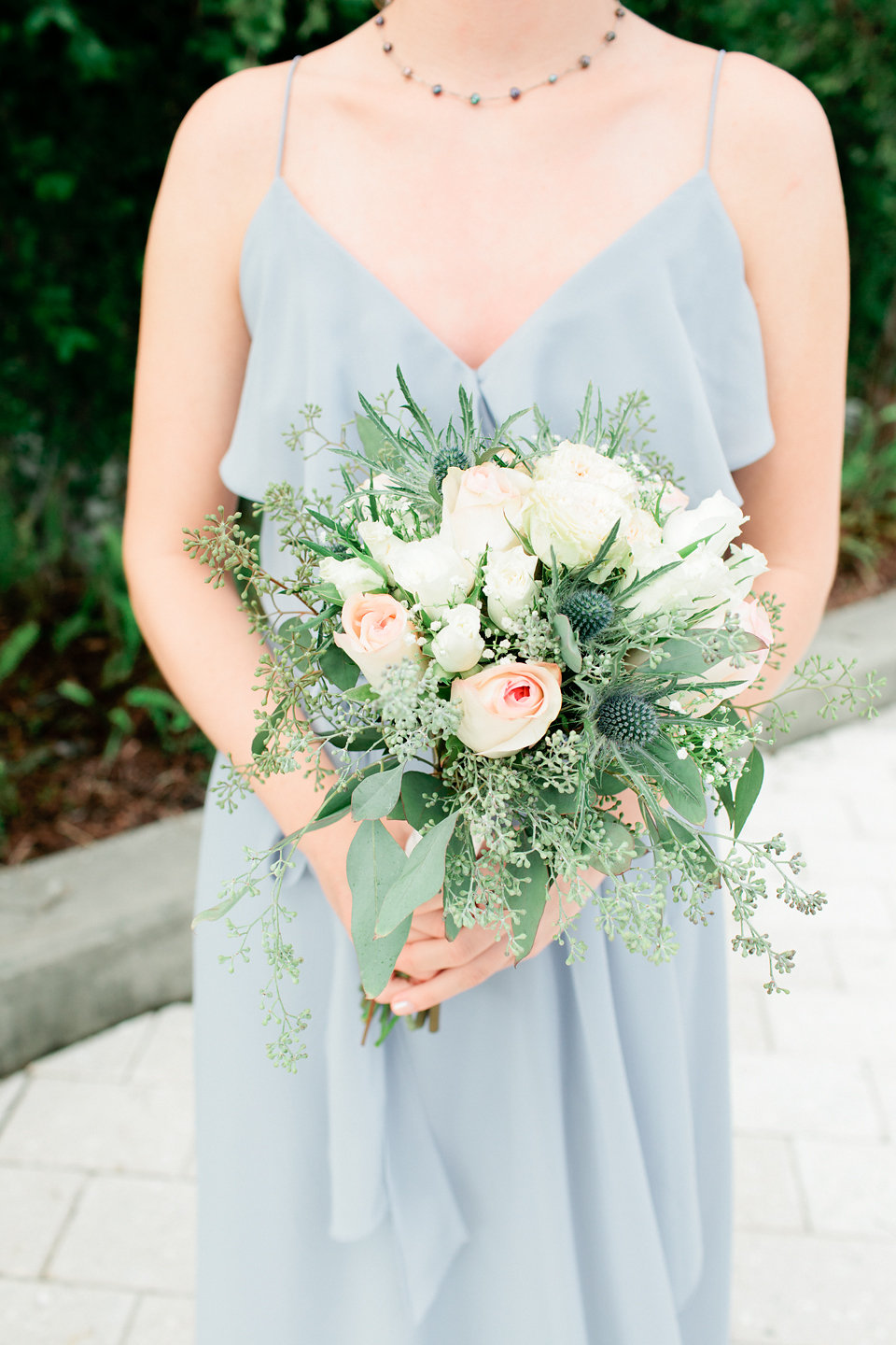 The bridesmaid bouquets consisted of blush and white roses, eucalyptus, and blue thistle.