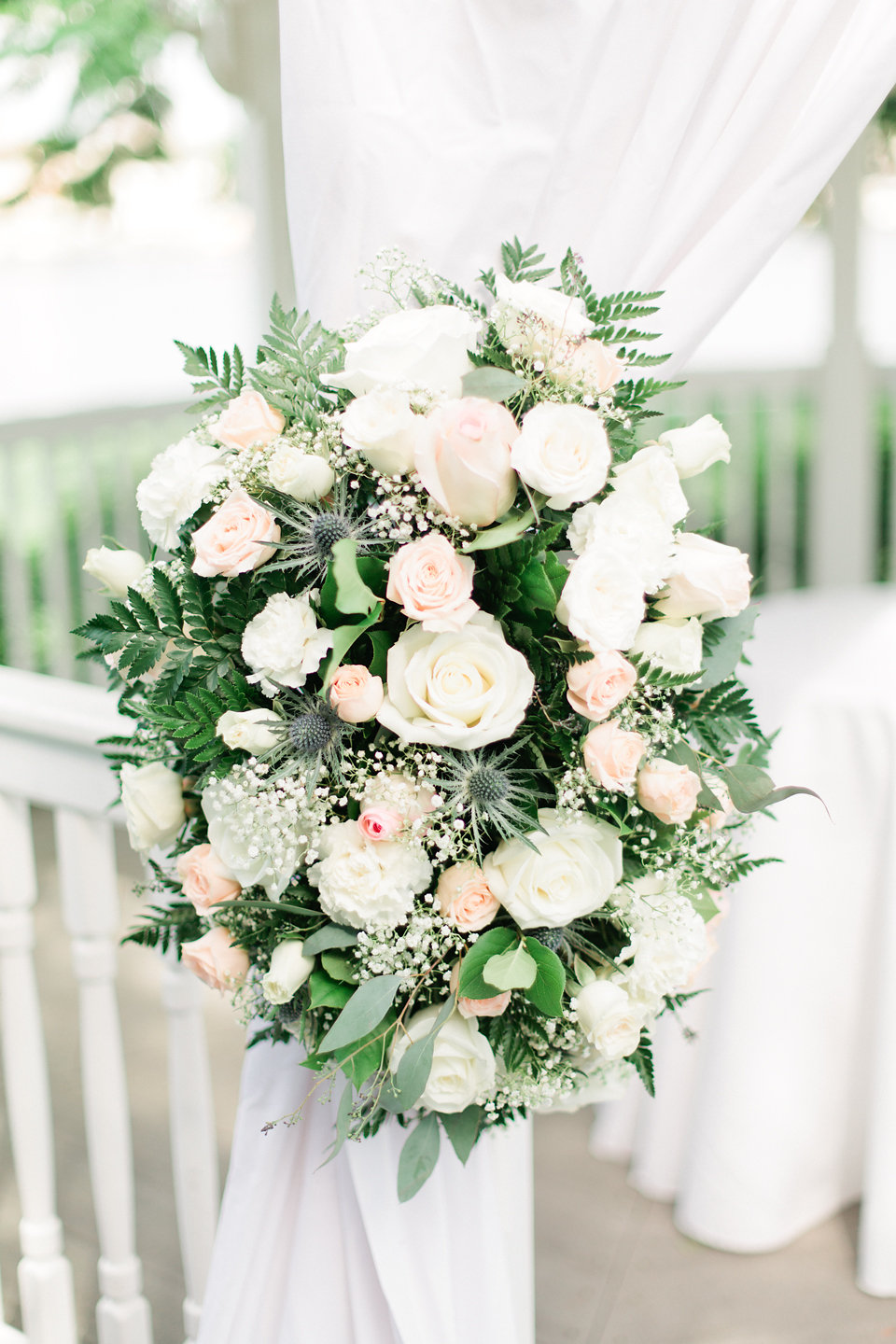 The ceremony floral arrangements included blush and white roses, baby's breath, blue thistle, and garden greenery.