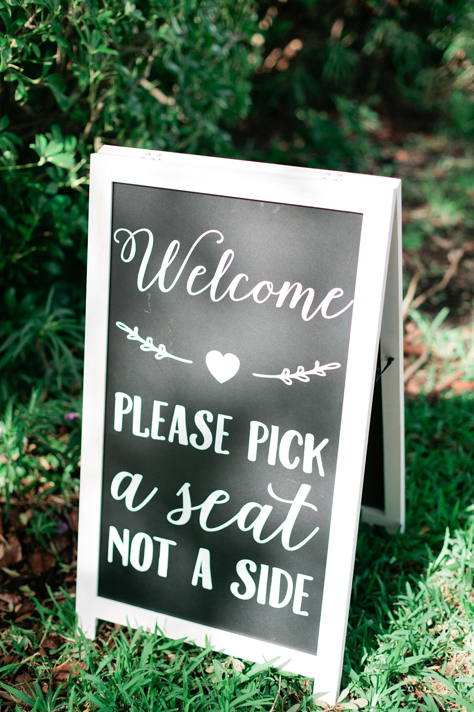 A chalkboard sign welcomed guests to choose any seat at the waterfront ceremony.
