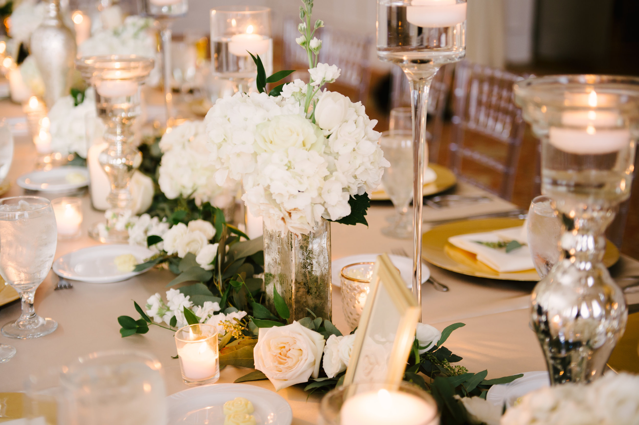 The garland from the ceremony aisle was repurposed on the long feasting tables inside the ballroom, and accented with neutral ivory blooms and soft candlelight.
