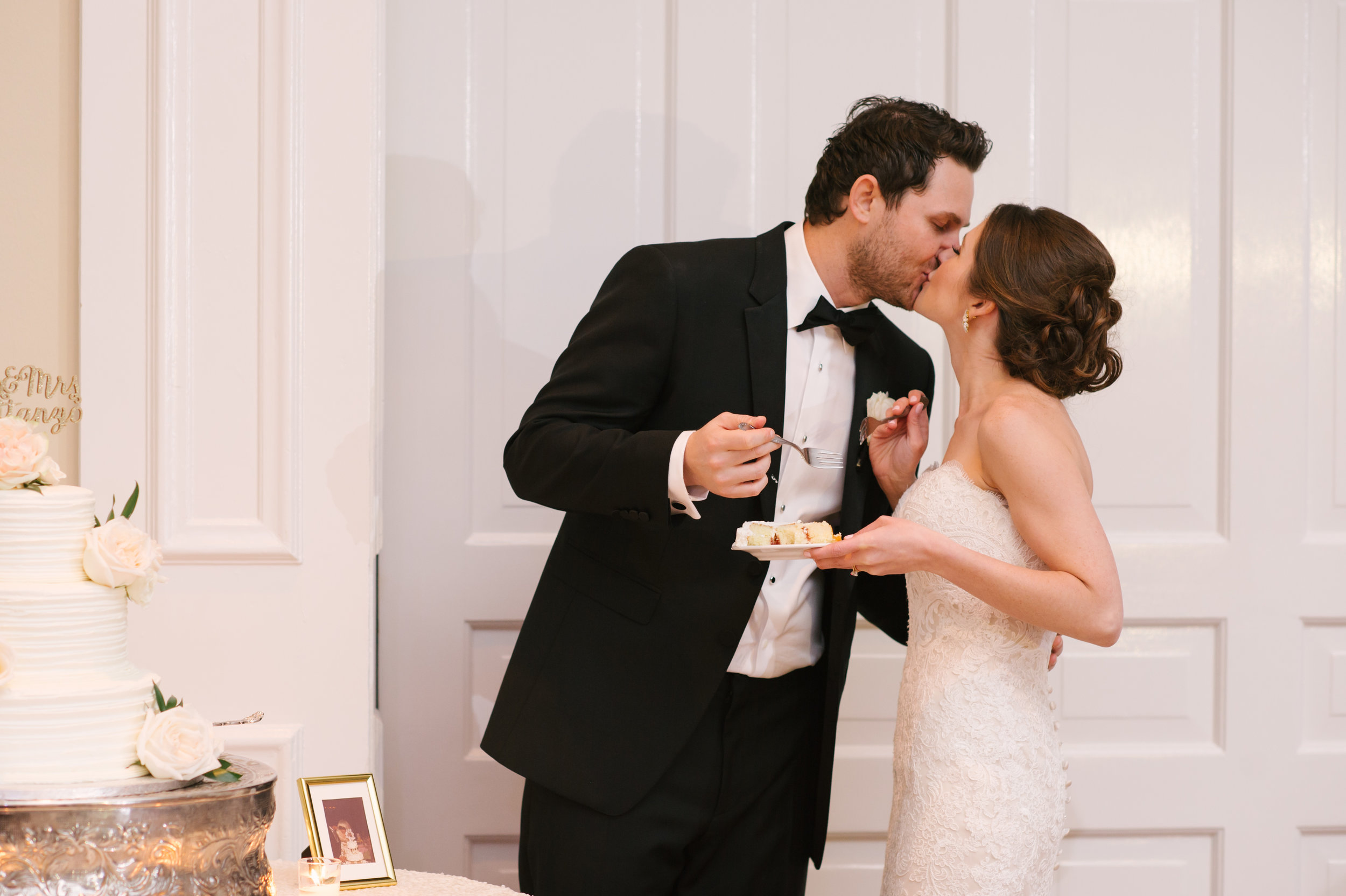 The couple sharing a bite of their beautiful (and delicious!) cake and a kiss!