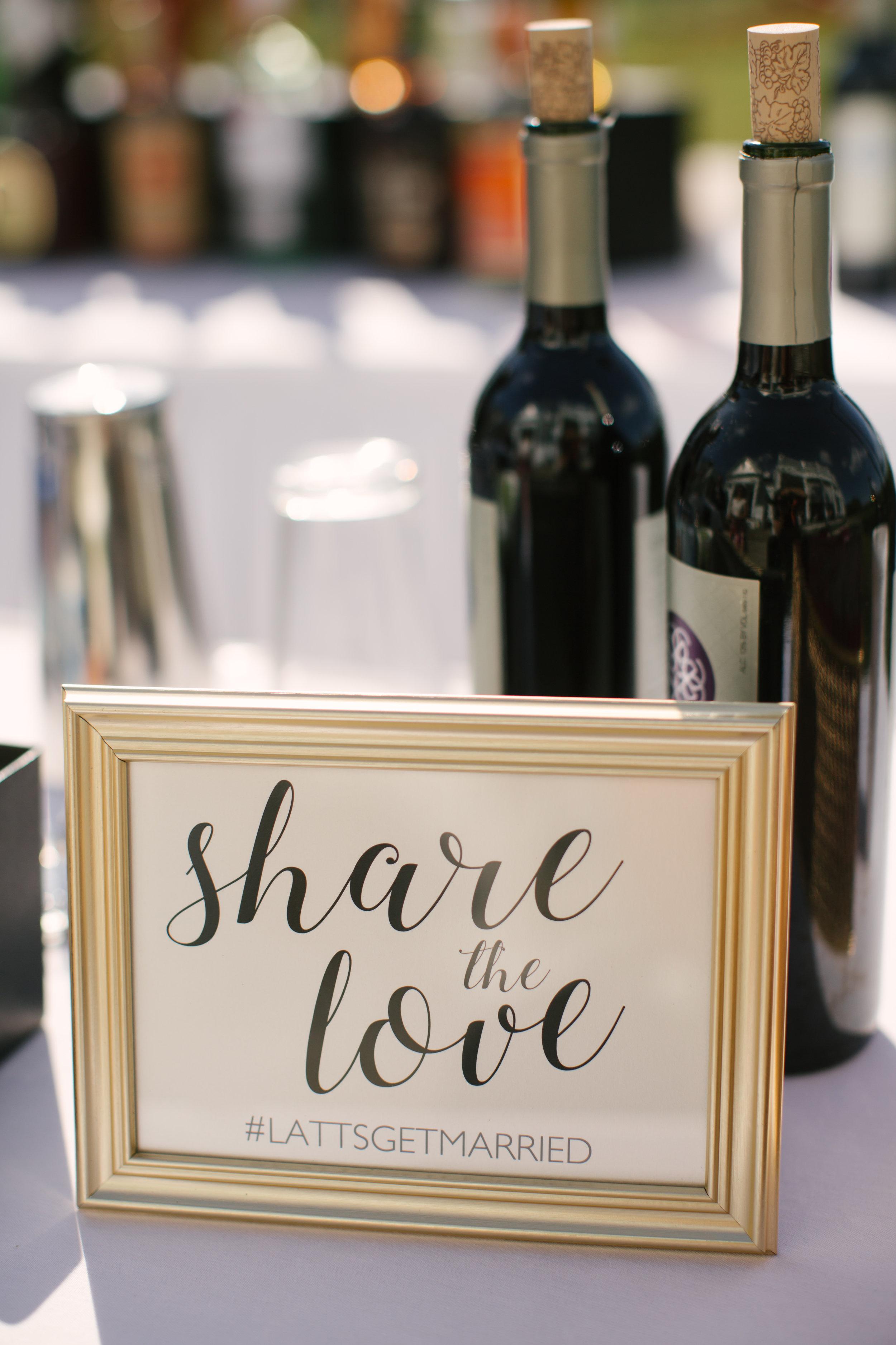 The couple's custom wedding hashtag in a gold framed sign on the bar.