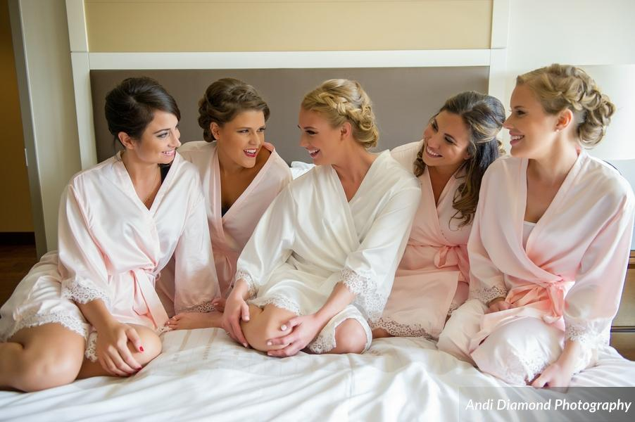 How sweet does the bridal party look in their matching silk robes with lace trim!?