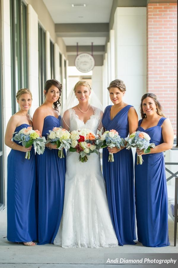 The bride stood out amongst her bridesmaids in sky blue dresses in different silhouettes, complimented by their bouquets of peach, orange, and dusty blue florals.