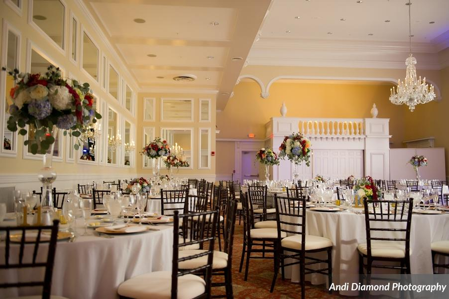 Mahogany Chiavari chairs sat at tables with crisp white linens, complimented with pops of the couple's wedding colors in large floral arrangements.