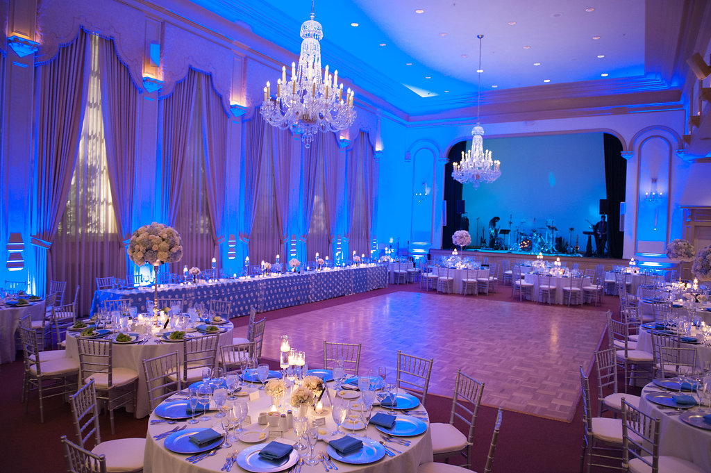 A formal plated meal was served at tables adorned with neutral and soft blue florals, beneath crystal chandeliers in the stunning ballroom at Palma Ceia.