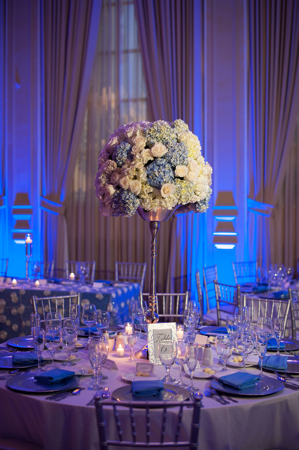 An abundance of hydrangea, roses, and candles were accented by uplighting, in the couple's signature Carolina blue.