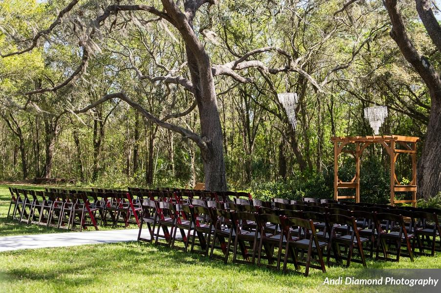 """Oak trees dripping in Spanish moss surrounded the ceremony space and crystal chandeliers hung above the couple as they said """"I do""""."""