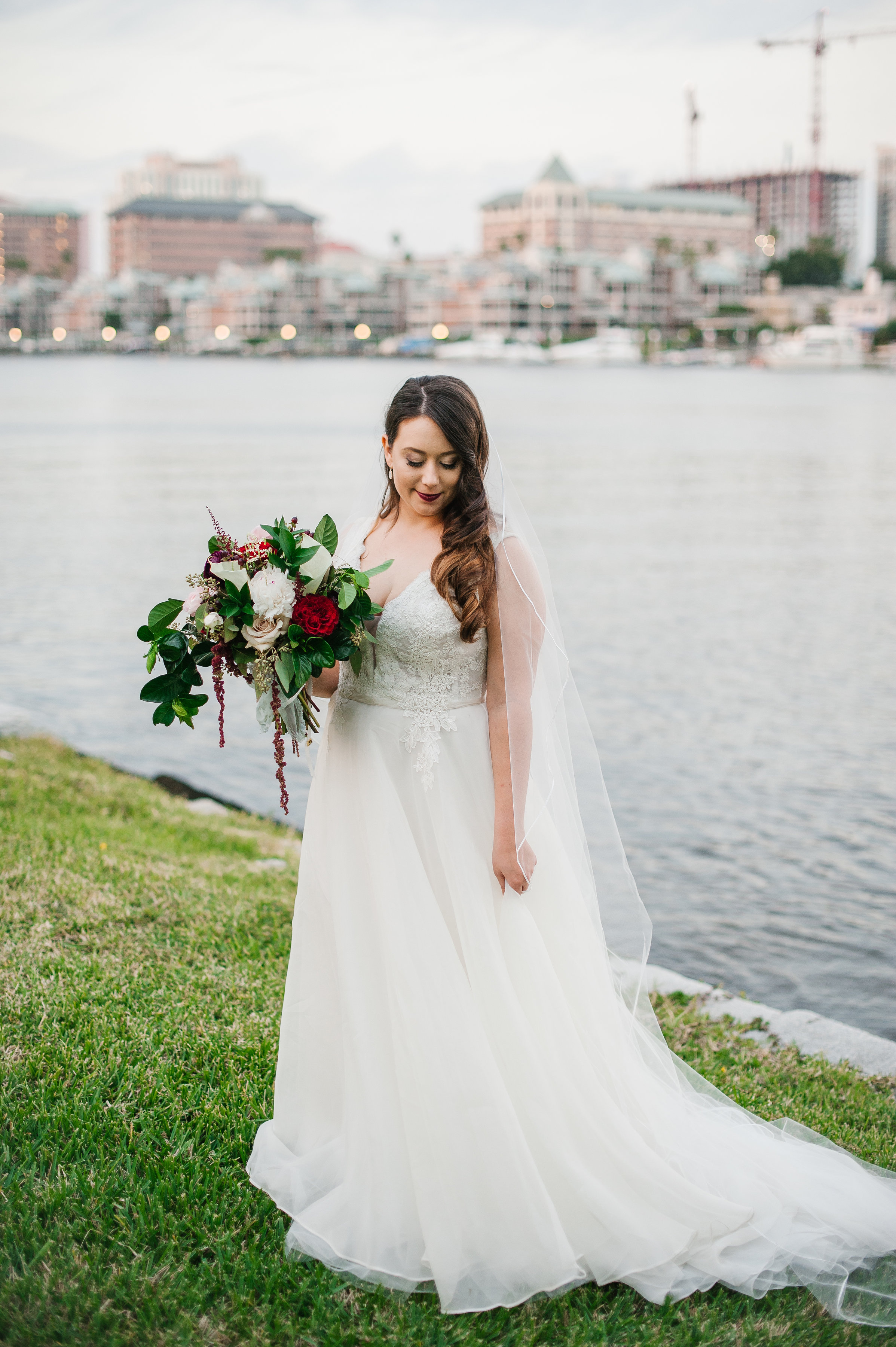 The bride wore a lace and tulle gown with a plunging lace illusion neckline;her dress was complimented by her organic bouquet of garden roses,greenery, and dripping amaranthus, with her look finished off with a dark berry lipstick to match the garnet and marsala tones in her bouquet.