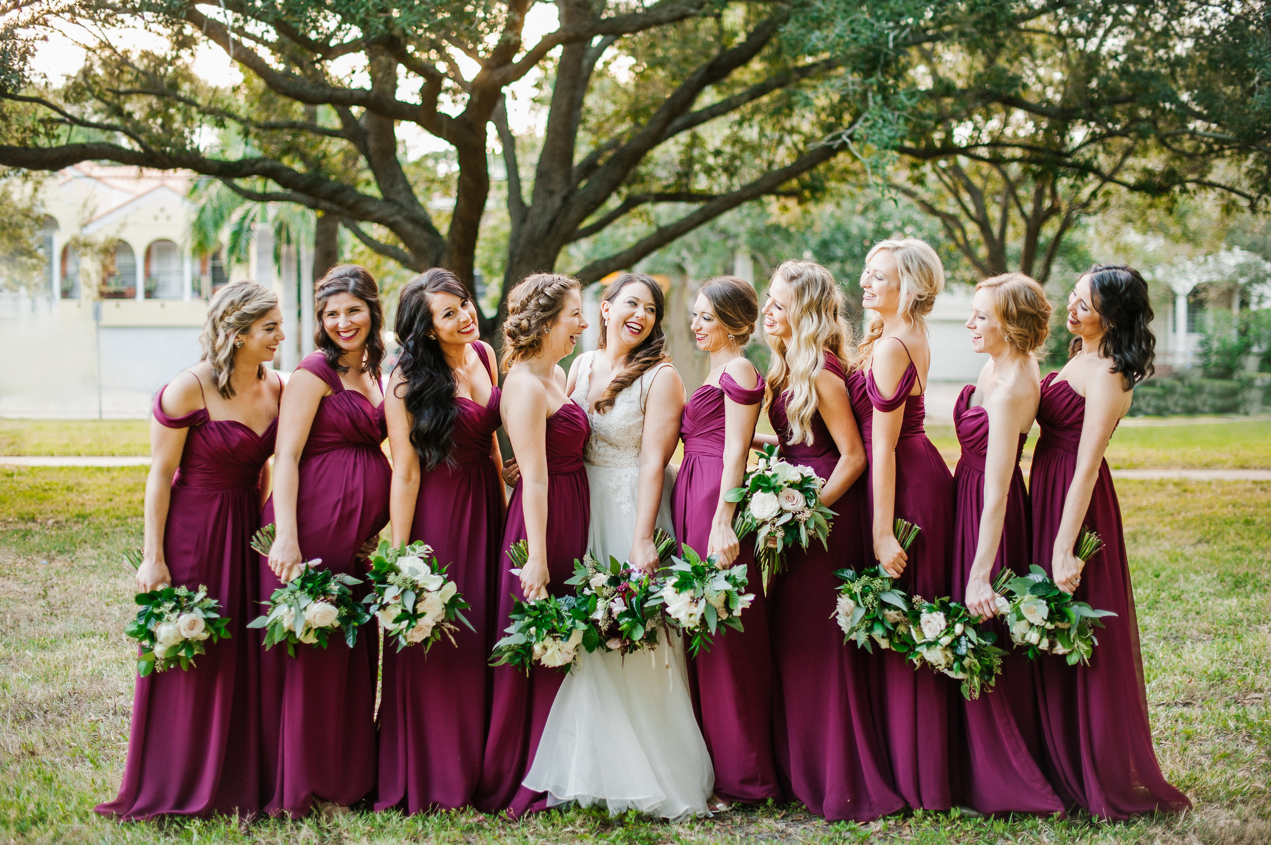 A gorgeous bunch of ladies in dark berry bridesmaid dresses, accented by they're bouquets with neutral blooms,dripping greenery, and marsala amaranthus.