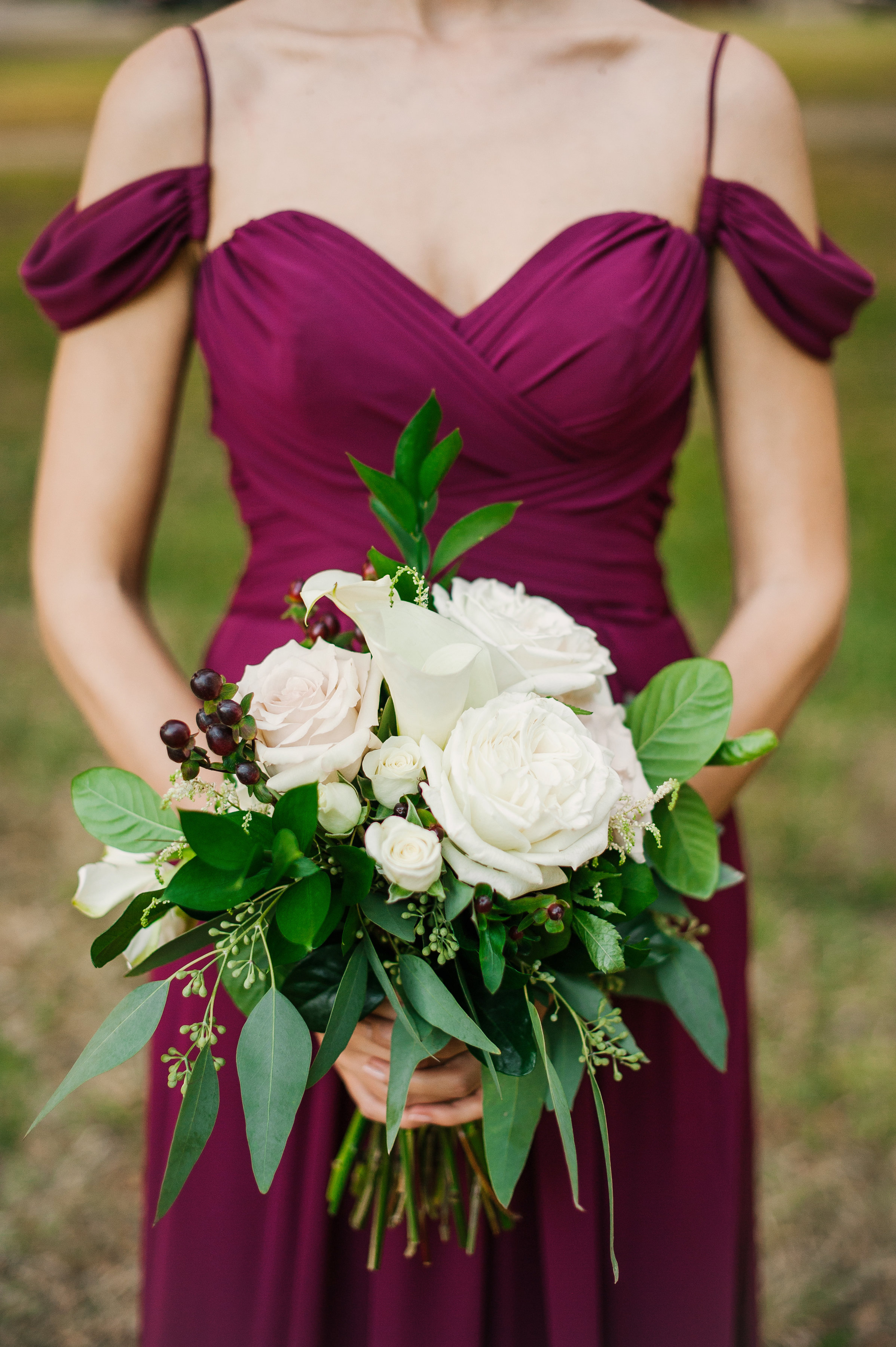 The bridesmaids bouquets were a mix of garnet and greenery with touches of ivory and blush florals.