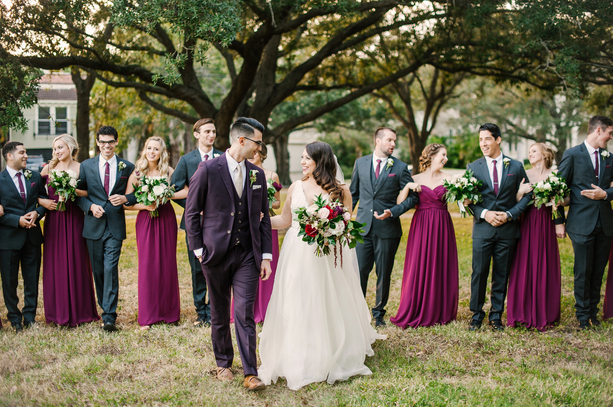The bride and groom complimented by their stylish wedding party in grey and cranberry tones.