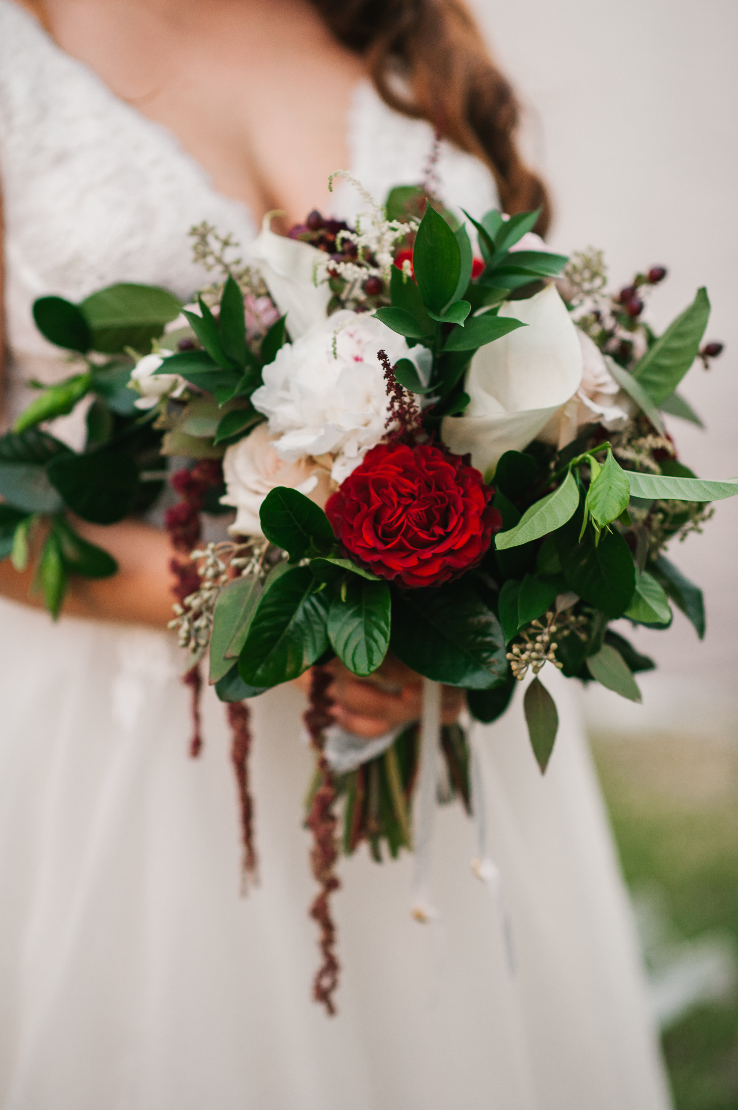 The bride's organic dripping bouquet looks stunning, and with dark reds throughout, pops against her ivory dress.