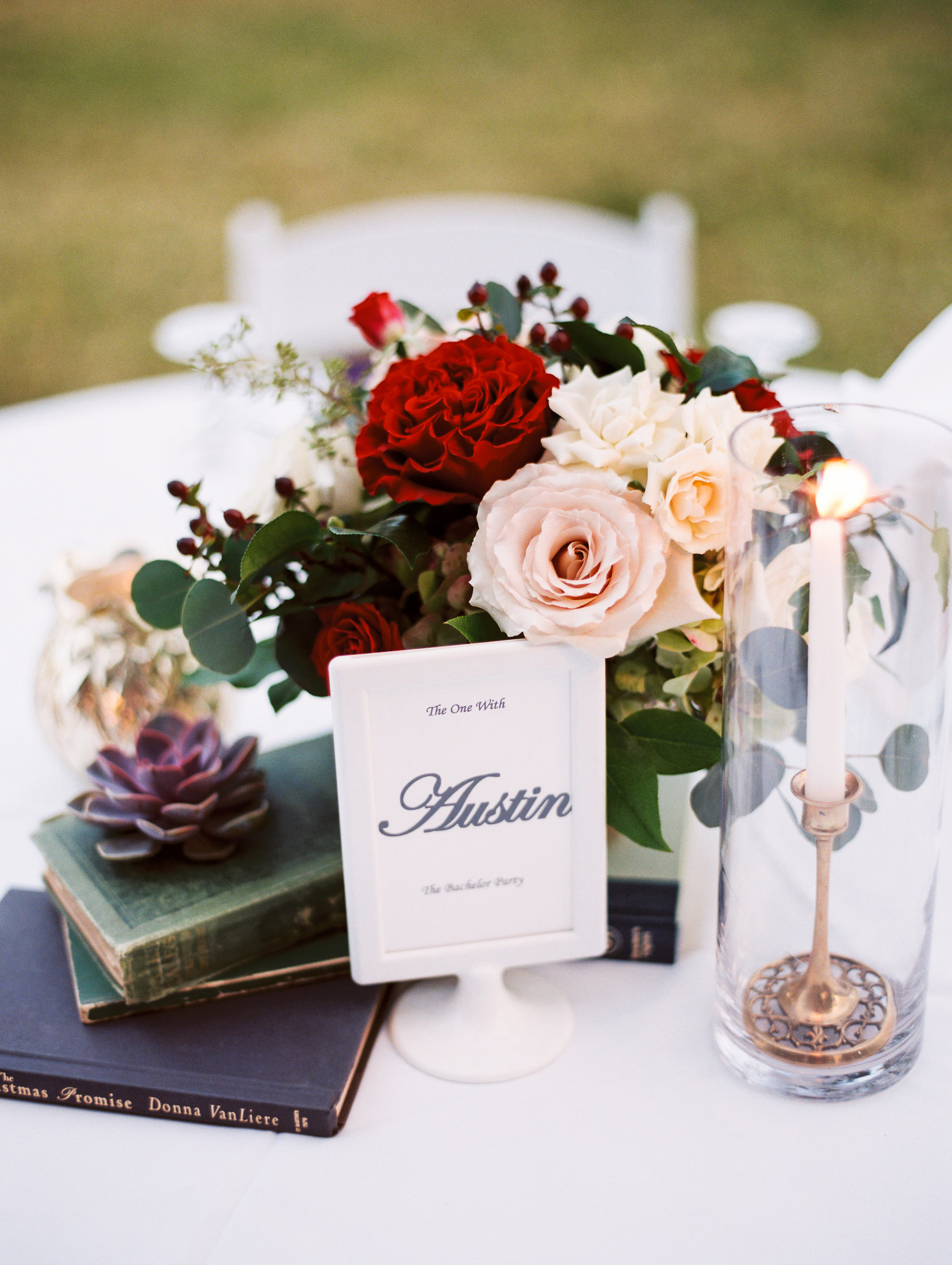 """The centerpieces with gold candlestick holders and vintage books gave an elegant and romantic feel to the tables;while the table """"numbers"""" were places and things special to the couple, infusing their personalities throughout the wedding."""