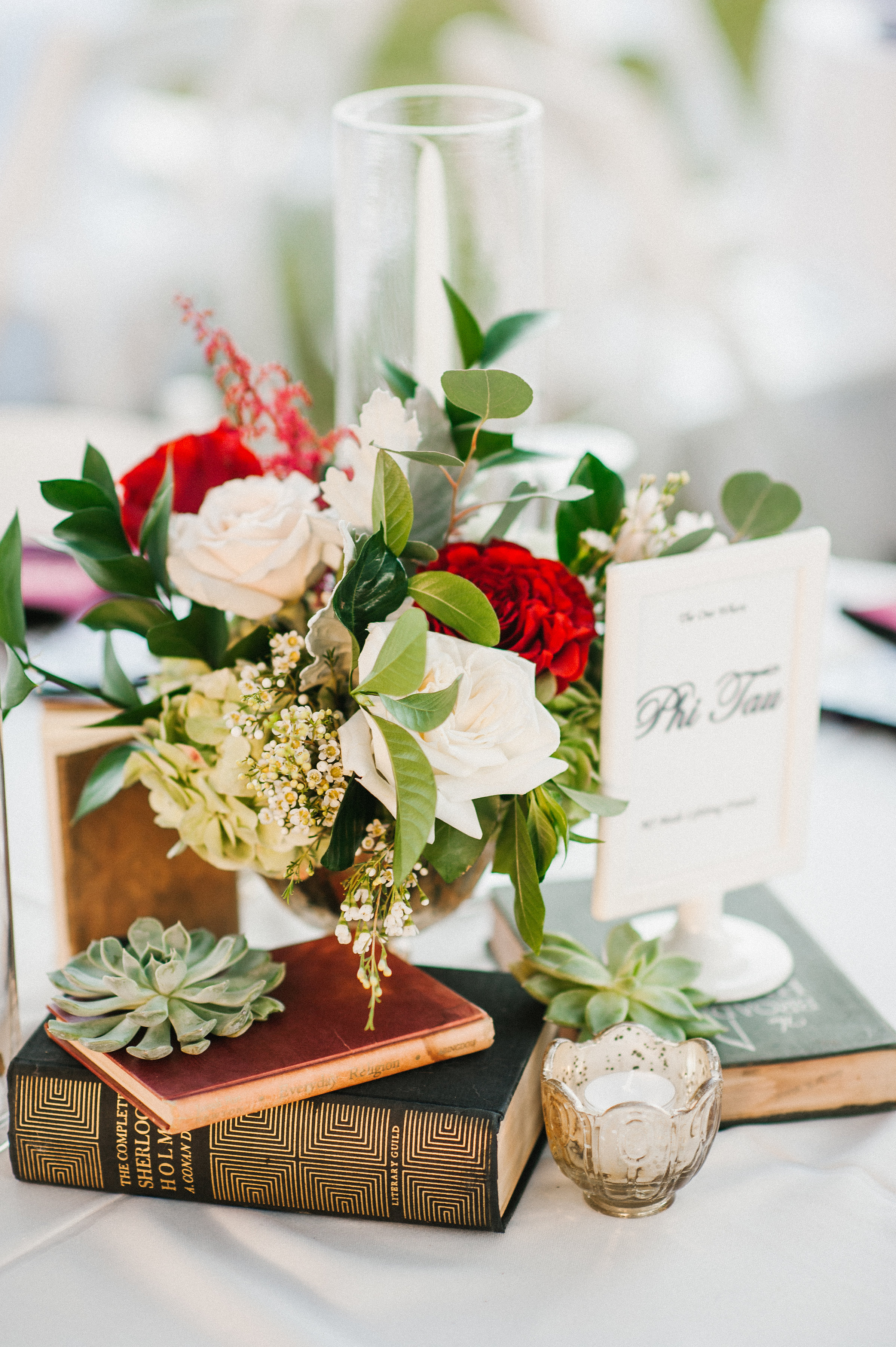 Bold reds and dark greens popped against the white table linens,accented with gold mercury glass and gold candle holders.