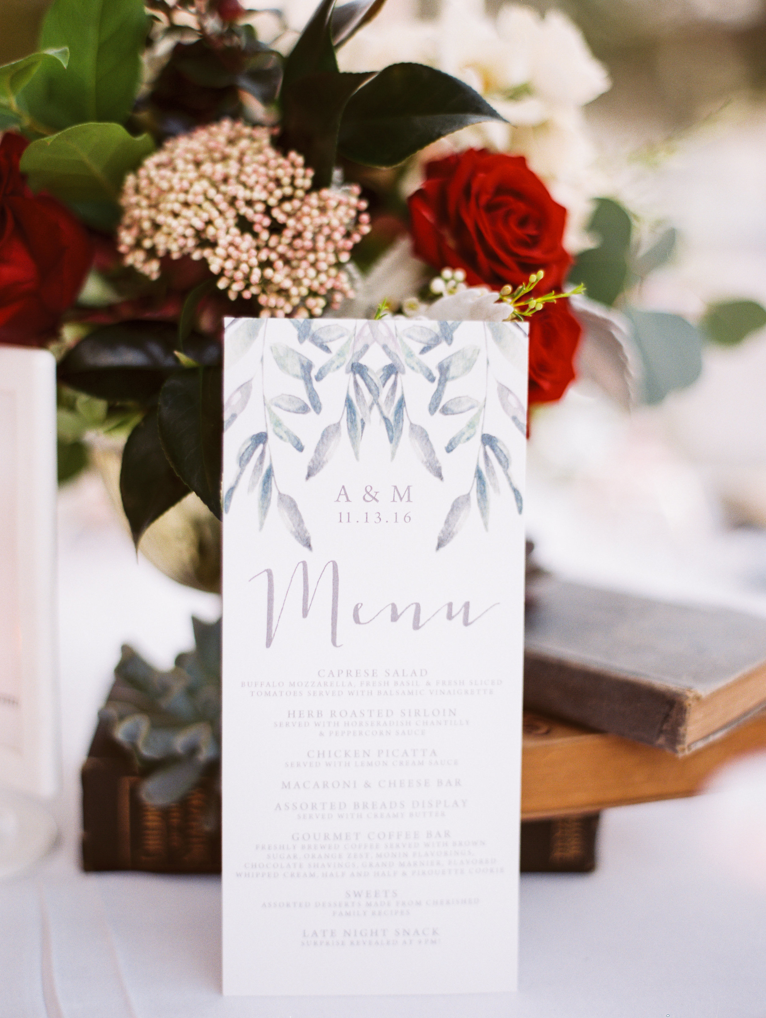 Menu cards framed with greenery displayed at every place setting for guests.