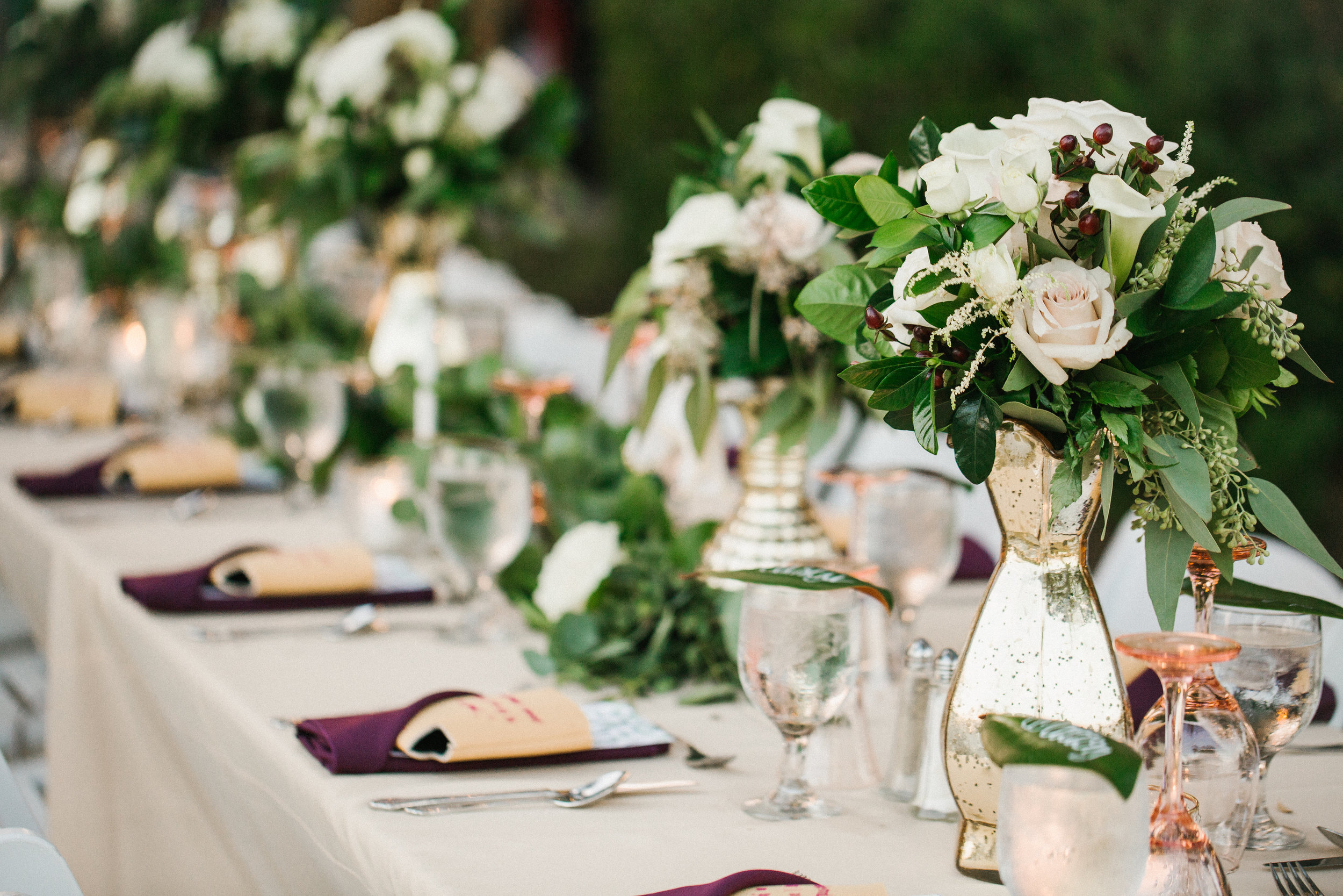 The wedding party sat at a long feasting table which was dripped in greenery and soft gold mercury glass, with those pops of marsala throughout.