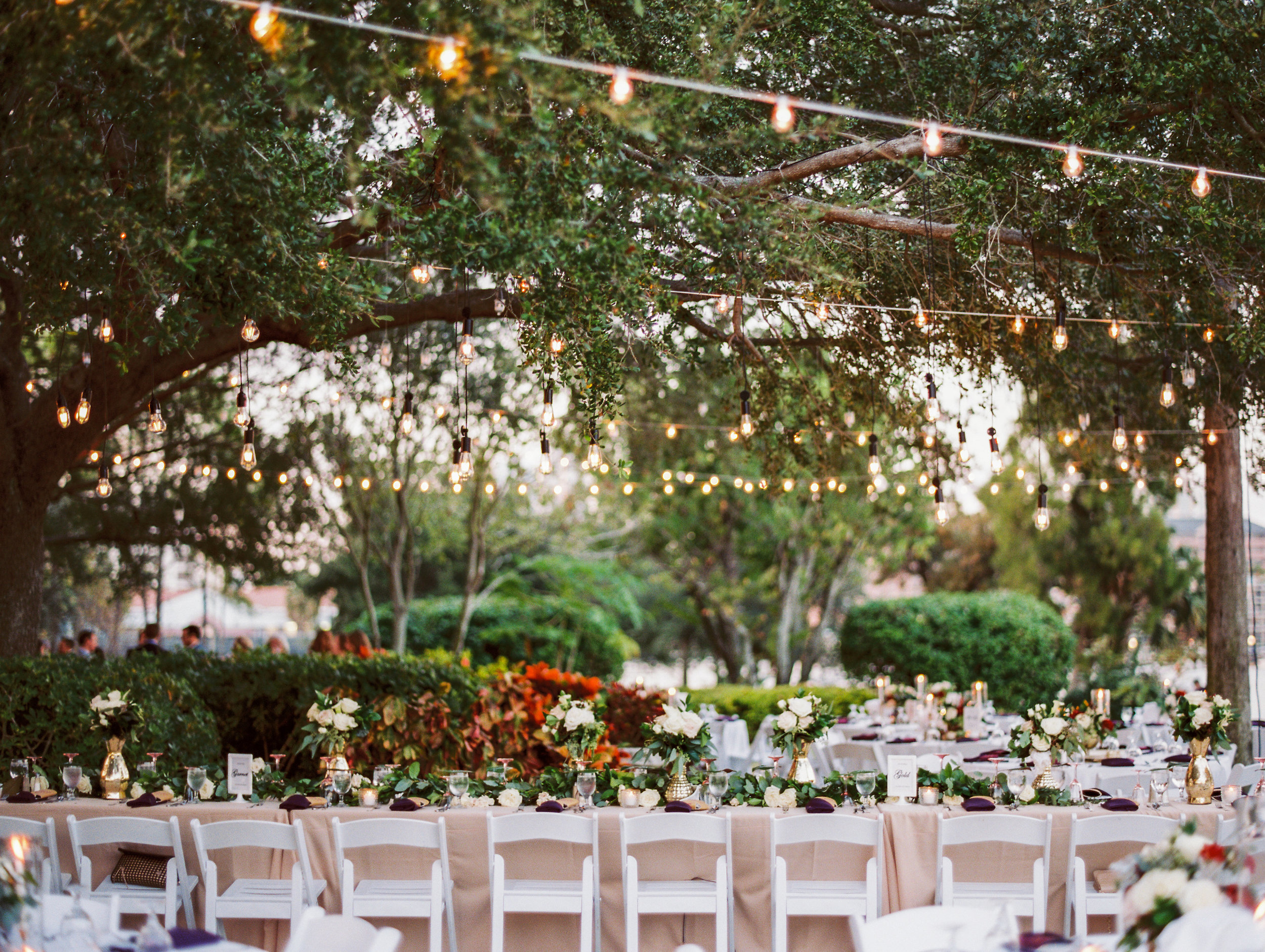 Edison lights,strung amongst the oak trees above the tables, paired with the glow of candlelight on mercury glass made this outdoor reception feel warm and romantic.