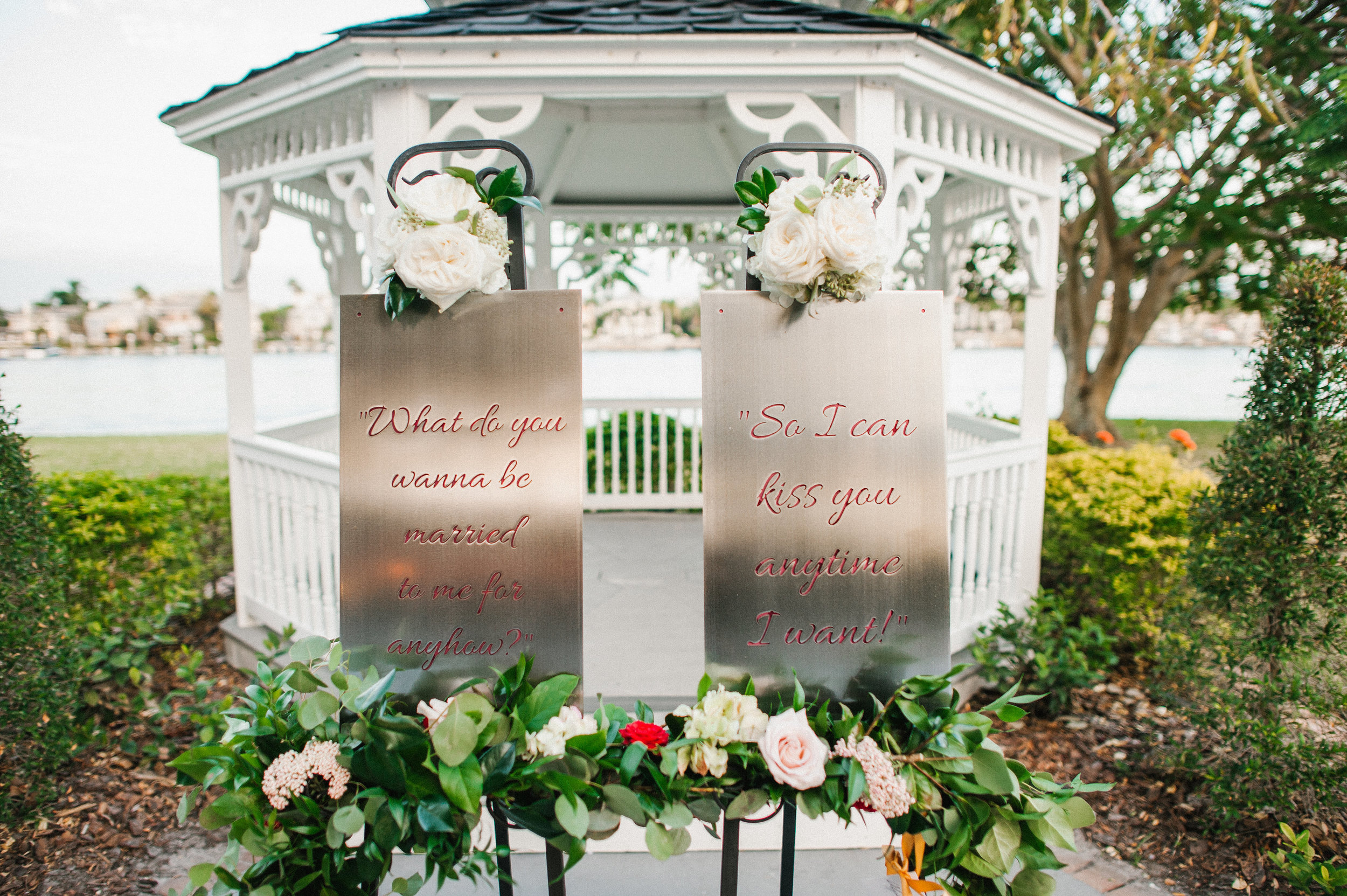 """The mother of the bride surprised the couple with custom garnet and gold metal signs with the sweetest quote from one of their favorite movies. The signs read """"What do you wanna be married to me for anyhow?"""" """"So I can kiss you anytime I want!"""" and were draped in complimentary florals and greenery,and sat behind the bride and groom during the reception (so sweet!)"""