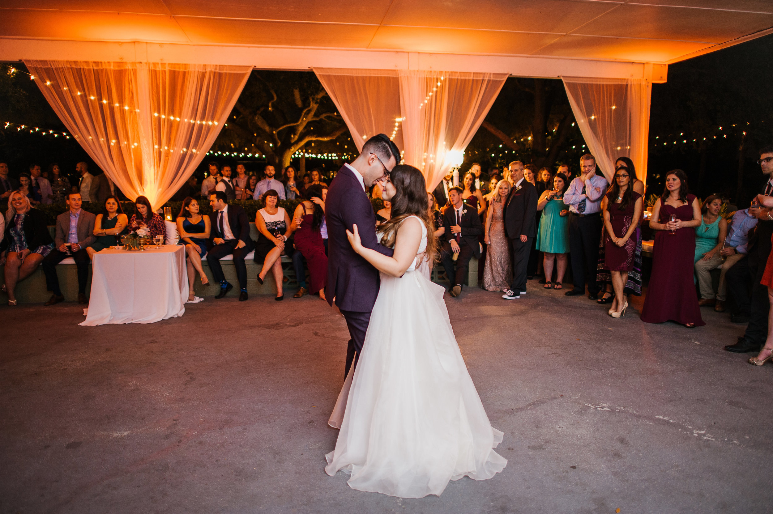 The couple sharing their first dance while surrounded by loved ones, romantic lighting, and chiffon drapery.