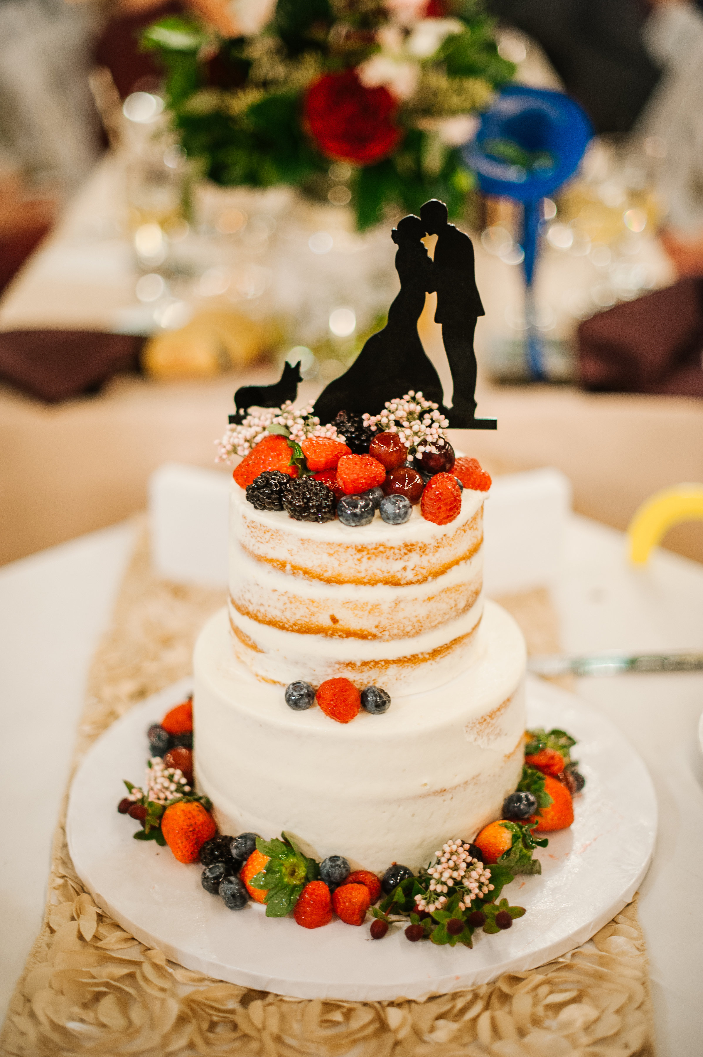 A two-tiered naked cake accented with dark berries and topped with a silhouette cake topper of the couple and their rescue pup Meagan!