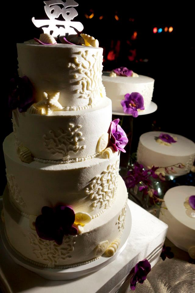 Several small cakes decorated with purple orchids led to a four tiered confection complete with chocolate seashells, piped coral fans, and of course more orchids!