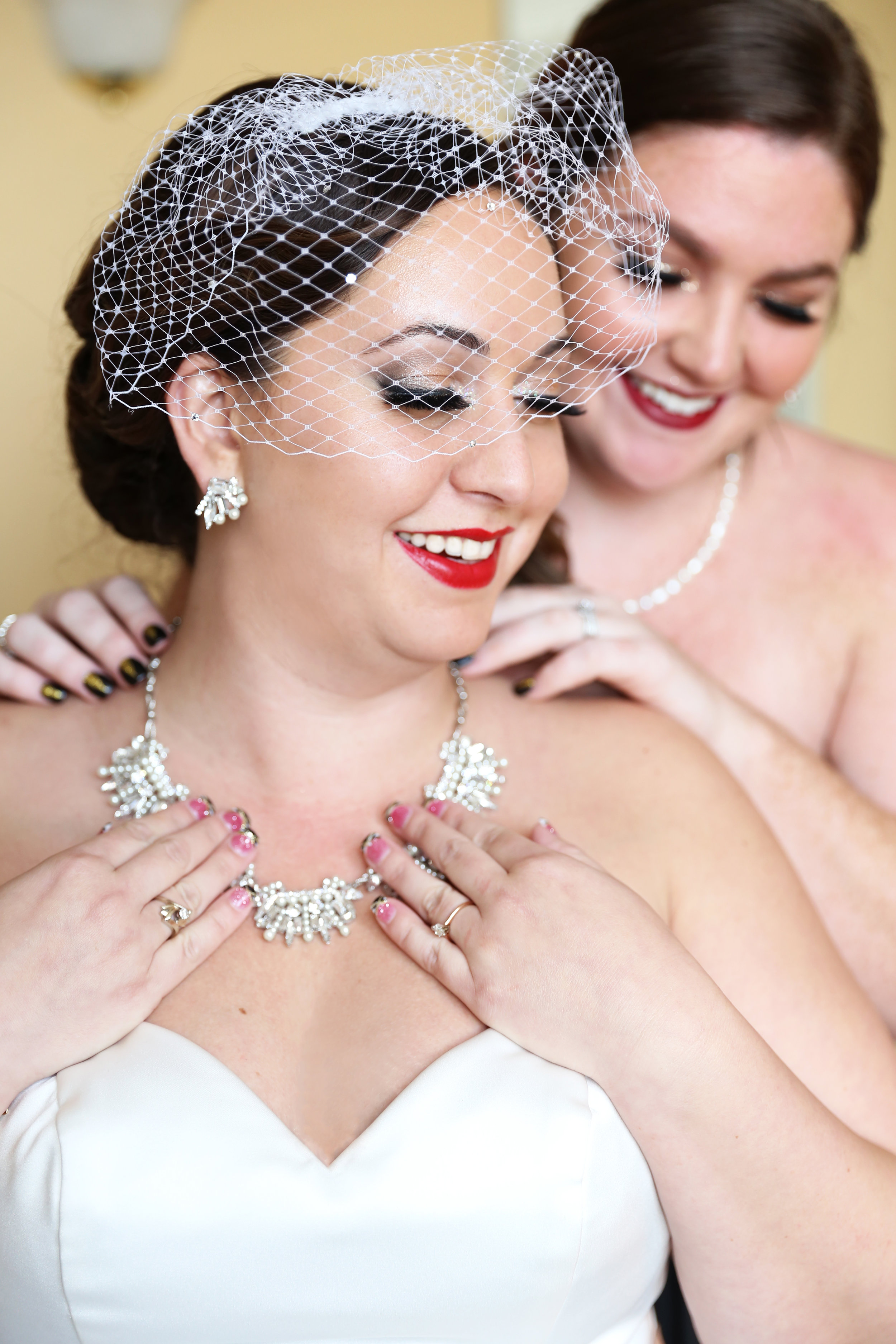 The bride boasted an Art Deco inspired necklace, a vintage birdcage veil, and a bright red lip that popped against all the black and white elements in the wedding!