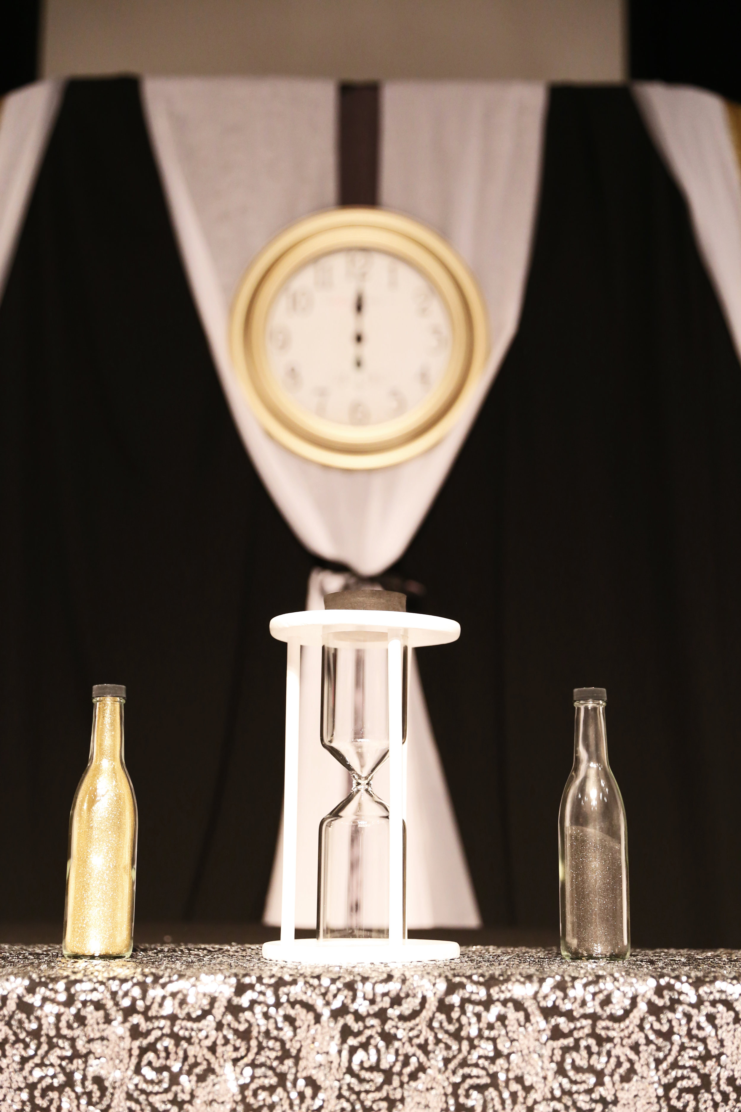 The ceremony aisle was accented with decorative clocks, and the pair partook in a unity ceremony wherein they blended sand into an hourglass, all in honor of the NYE countdown.