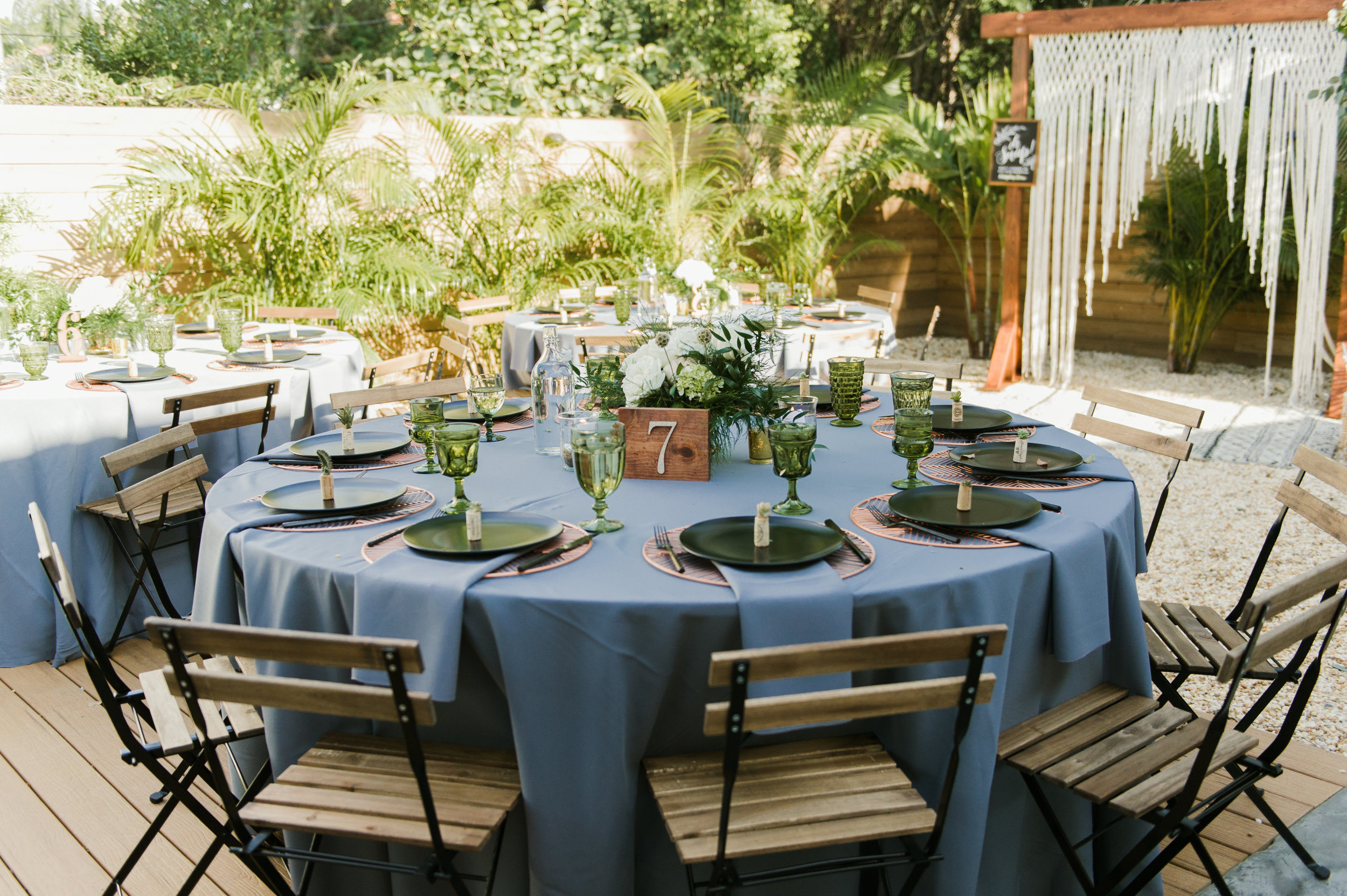 Tables were decorated with dusky blue linens, accented with green jewel tones, and featured natural wood chairs and table numbers.
