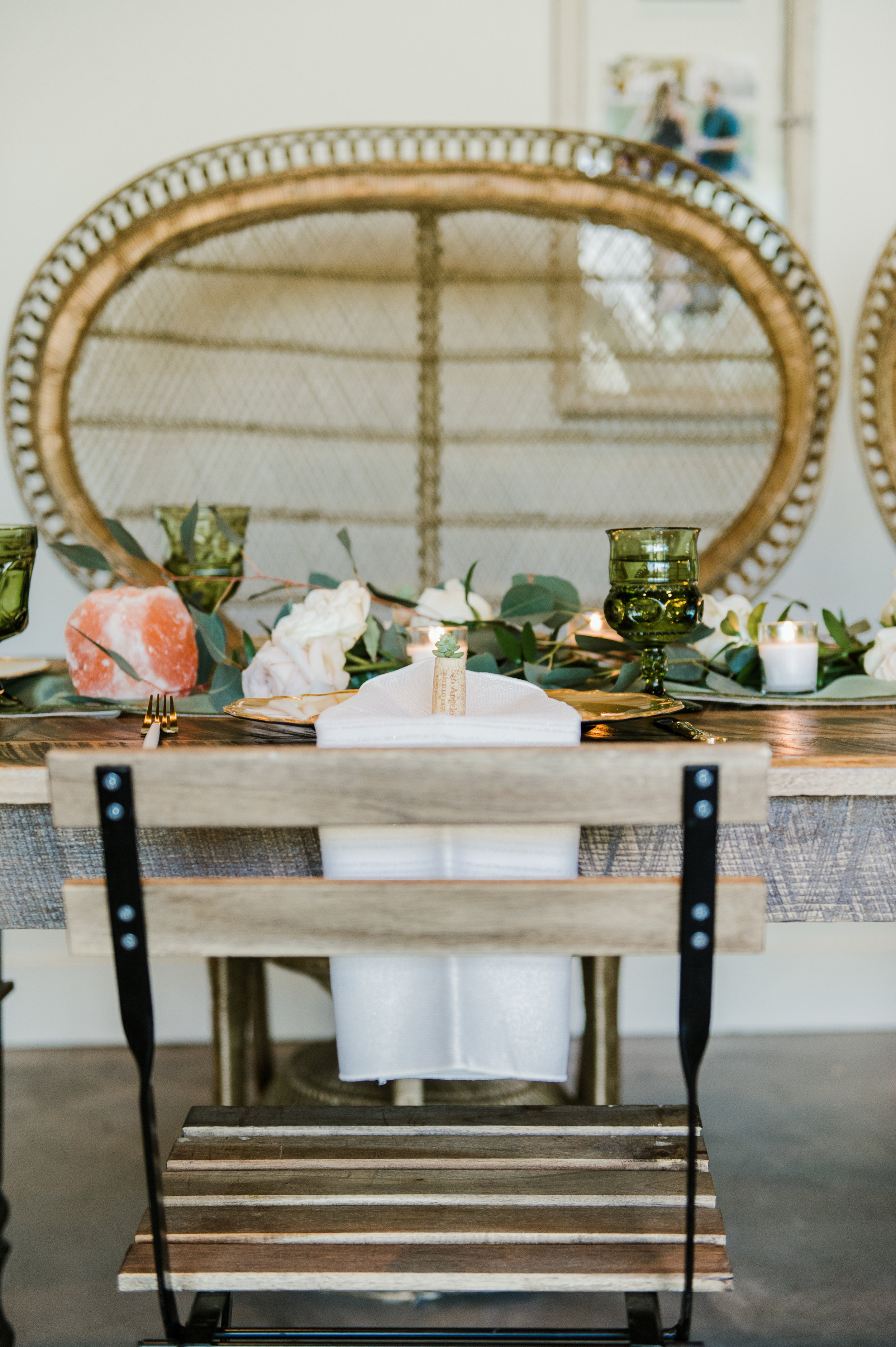 The couple sat at a feasting table with mis-matched emerald glasses, succulents, and plenty of flowing natural greenery.