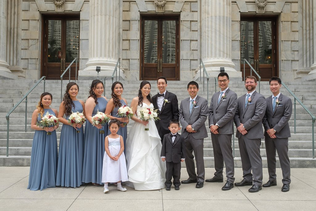 Blush and wine tones were found in the bouquets and boutonnieres,the bridesmaids wore soft blue-grey gowns, while the groomsmen sported grey tuxes with soft blue ties.