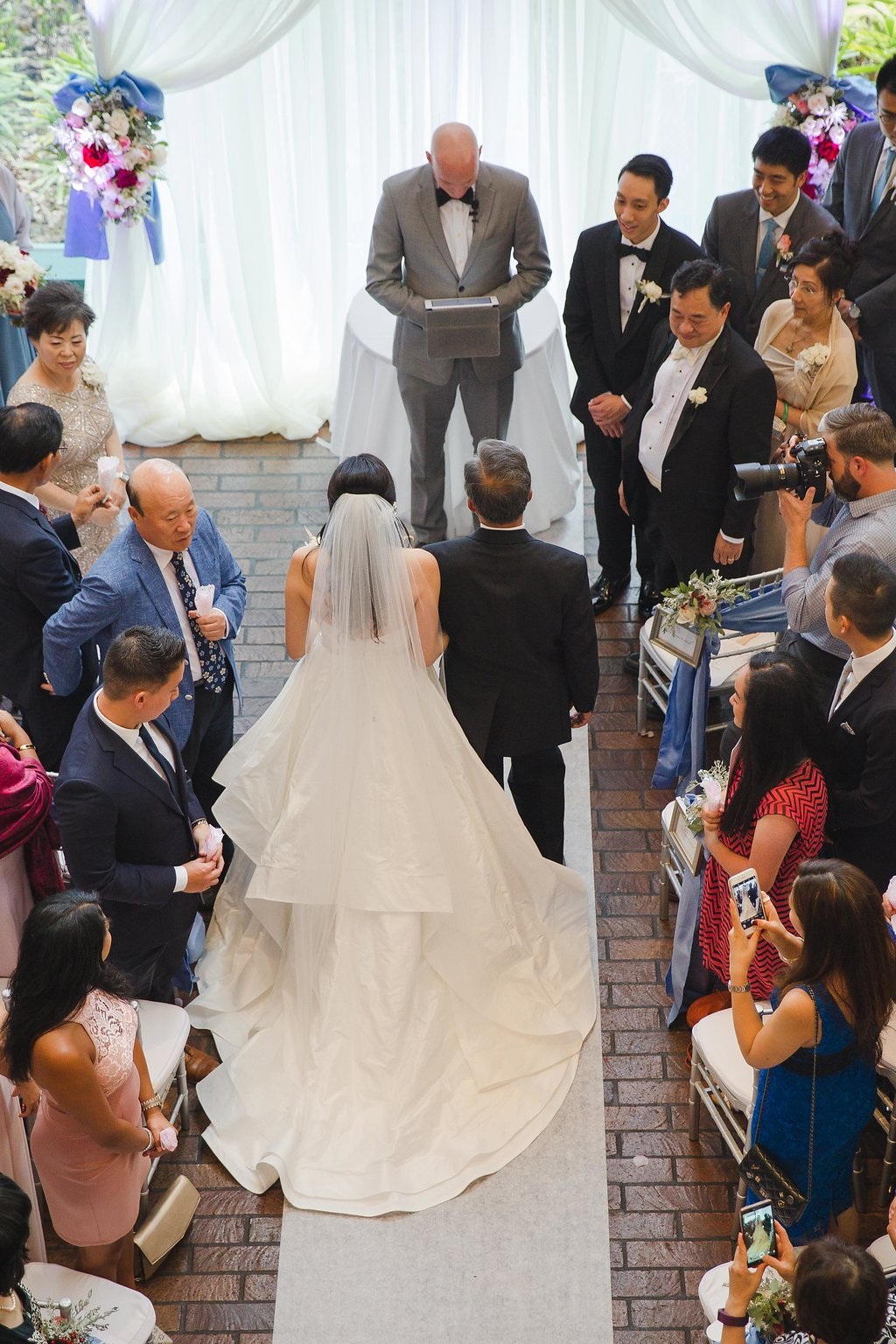 Although inclement weather brought their ceremony indoors, the expansive foyer of the performing arts center made for a stunning, grand backdrop.