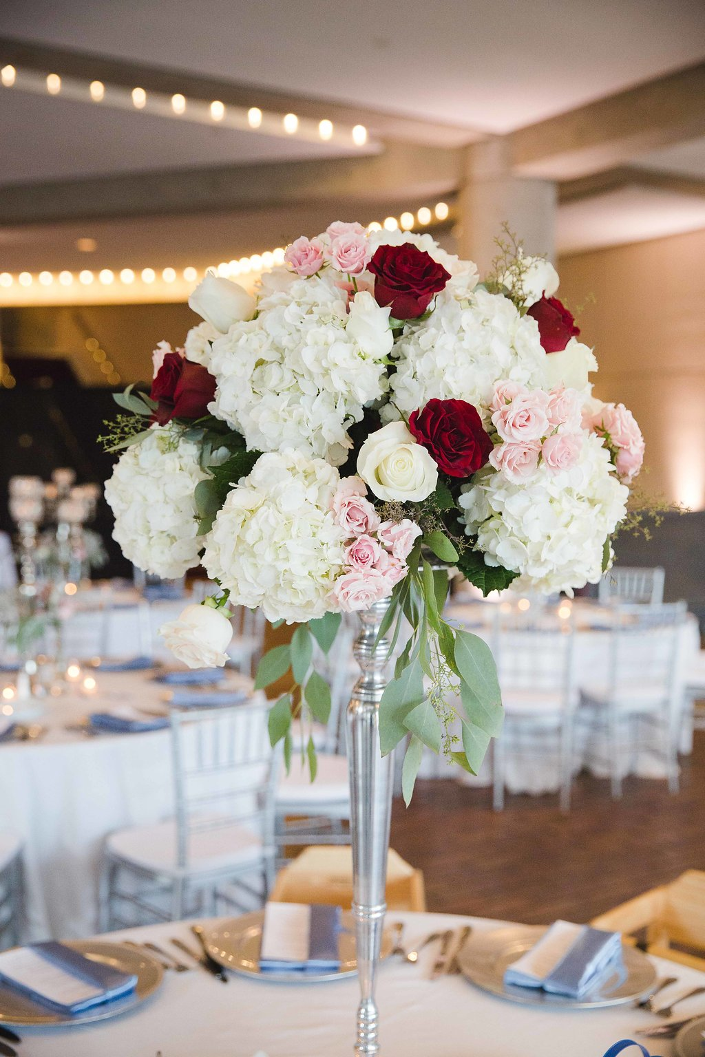 Shades of Blush and Merlot were natural choices (perfect for a wine-theme!) and blue-grey tones appeared in details like the bridesmaid dresses, napkins, and silk sashes down the ceremony aisle.
