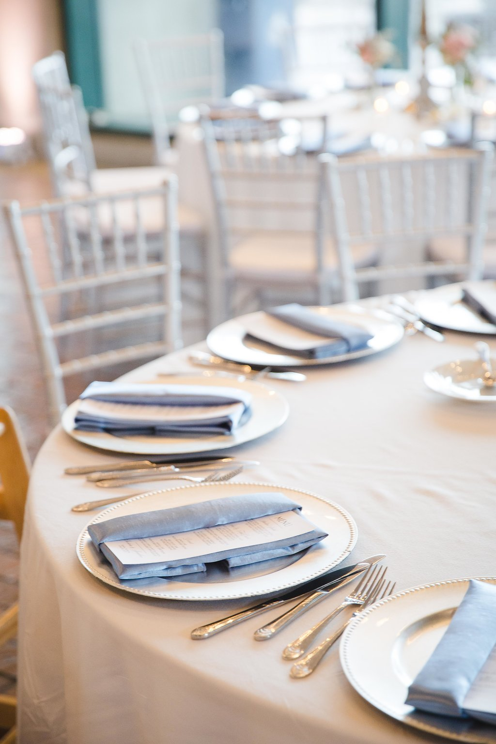 Crisp white menu cards with black script were tucked into dusty blue napkins at every place setting.