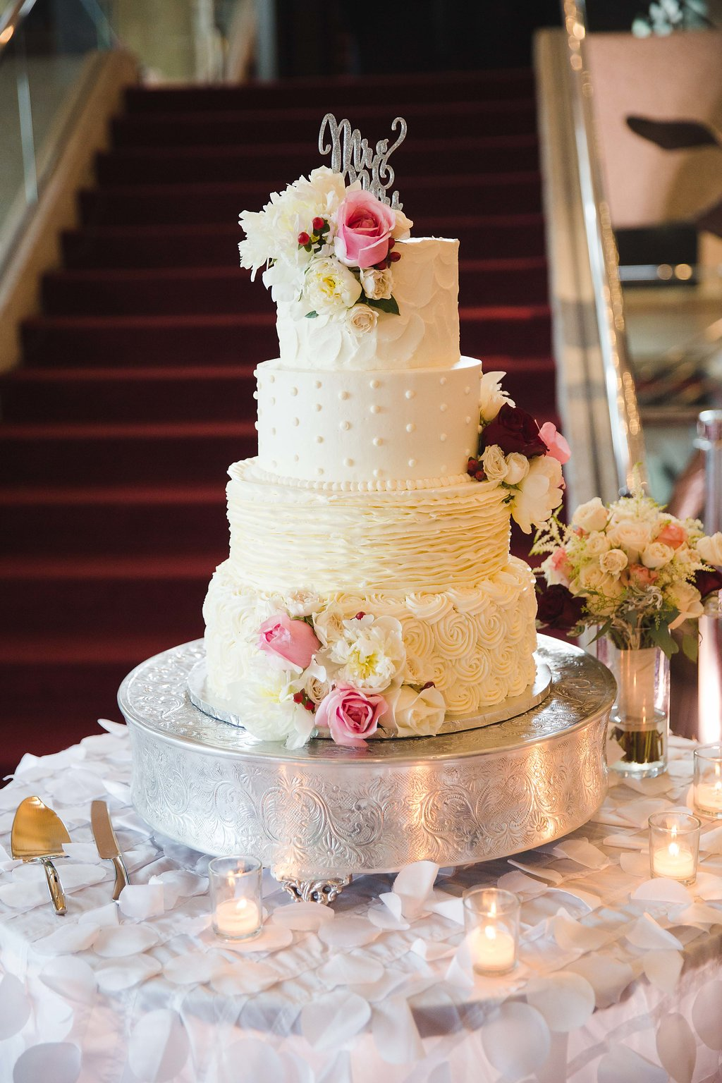 The cake was four layers of hand crafted confection perfection! It featured intricate piping details and complimenting florals, finished off with a silver 'Mr. & Mrs.' topper.