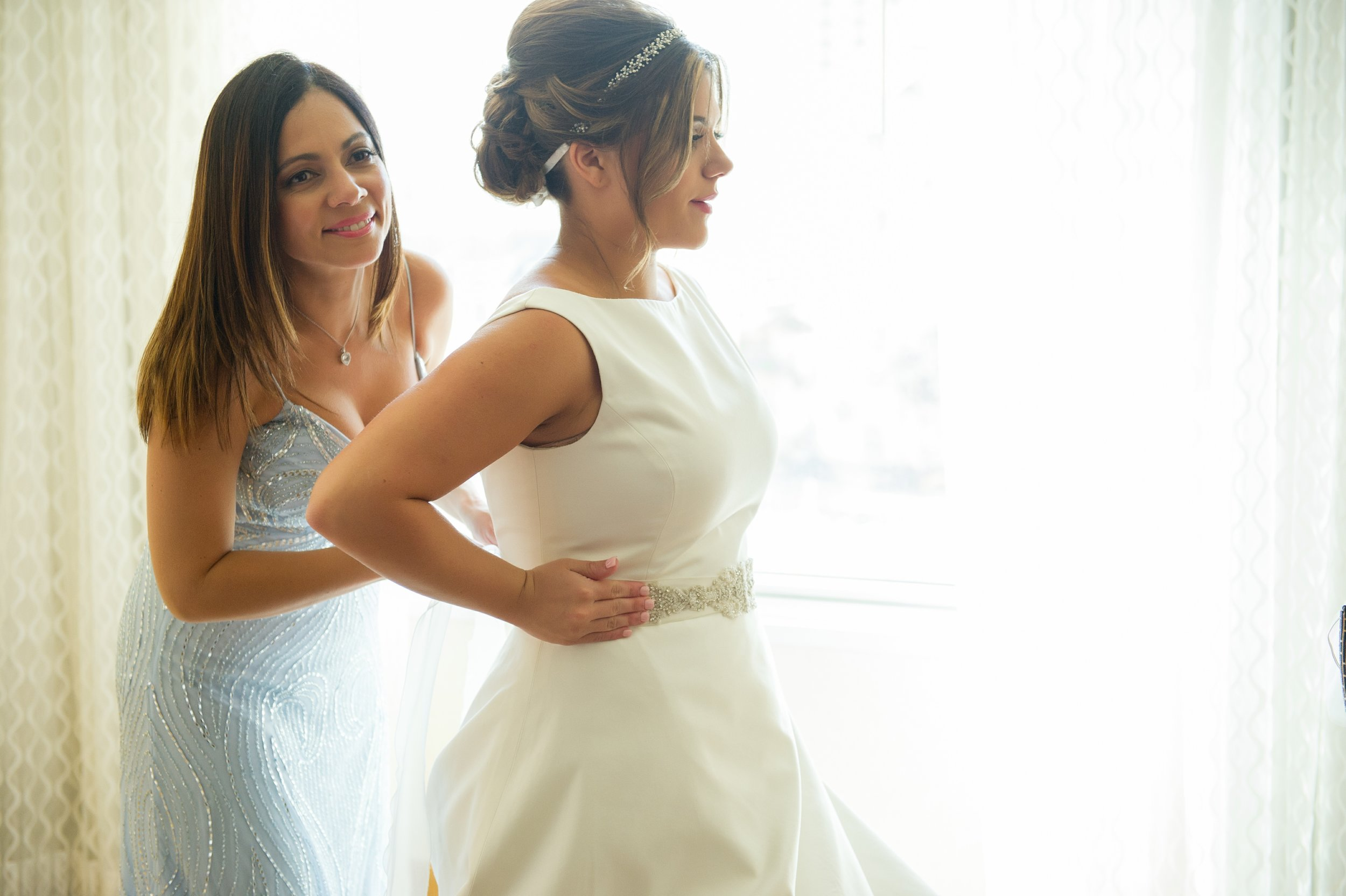 A sweet moment between mother and daughter, as the bride was helped into her dress.