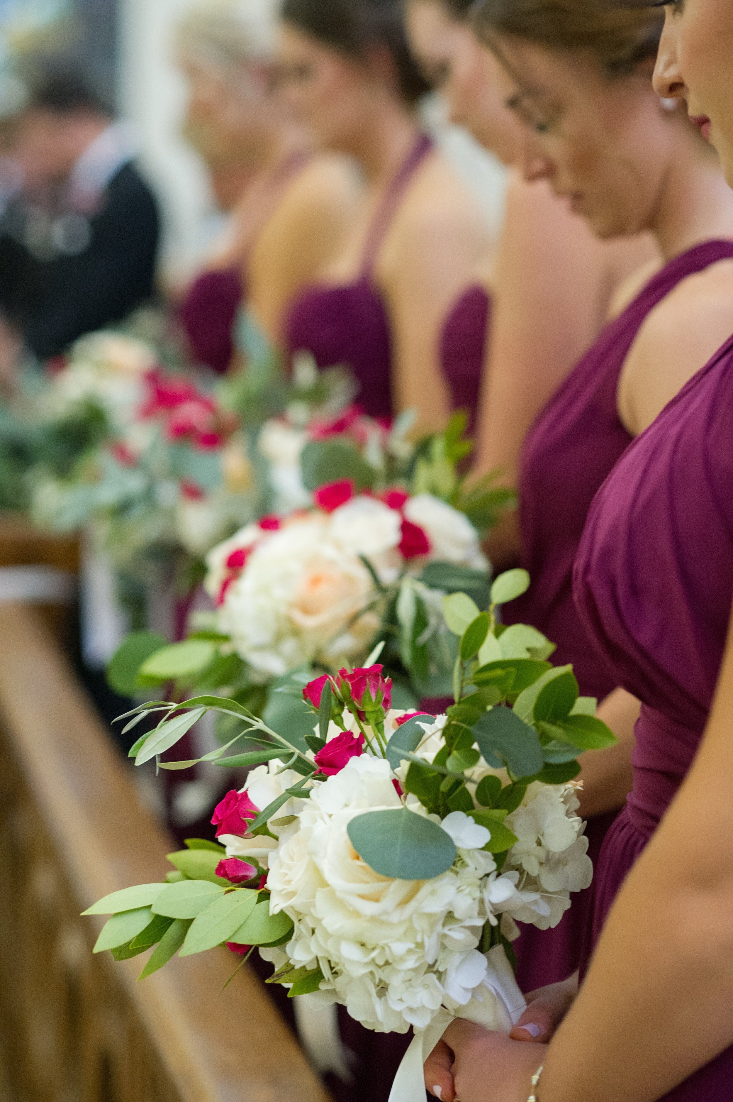 The bridesmaids wore berry colored dressed and carried bouquets of roses, hydrangea, spray roses, eucalyptus, and sage.