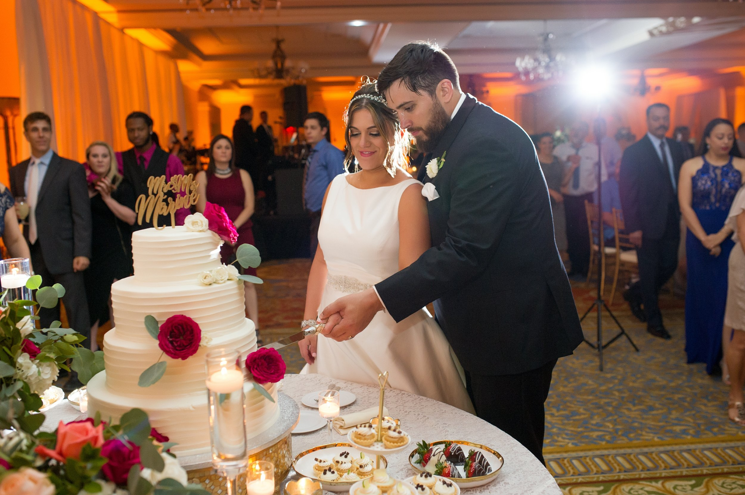 The cake was displayed on a gold mosaic cake stand and was surrounded with delicate trays of mini desserts, and abundant florals.