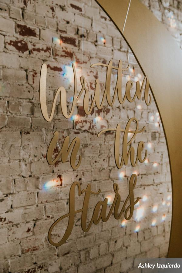 The couple had a custom golden crescent moon made for their backdrop, accented with a star sprinkled gobo on the exposed brick, and bistro lights overhead to simulate stars above.