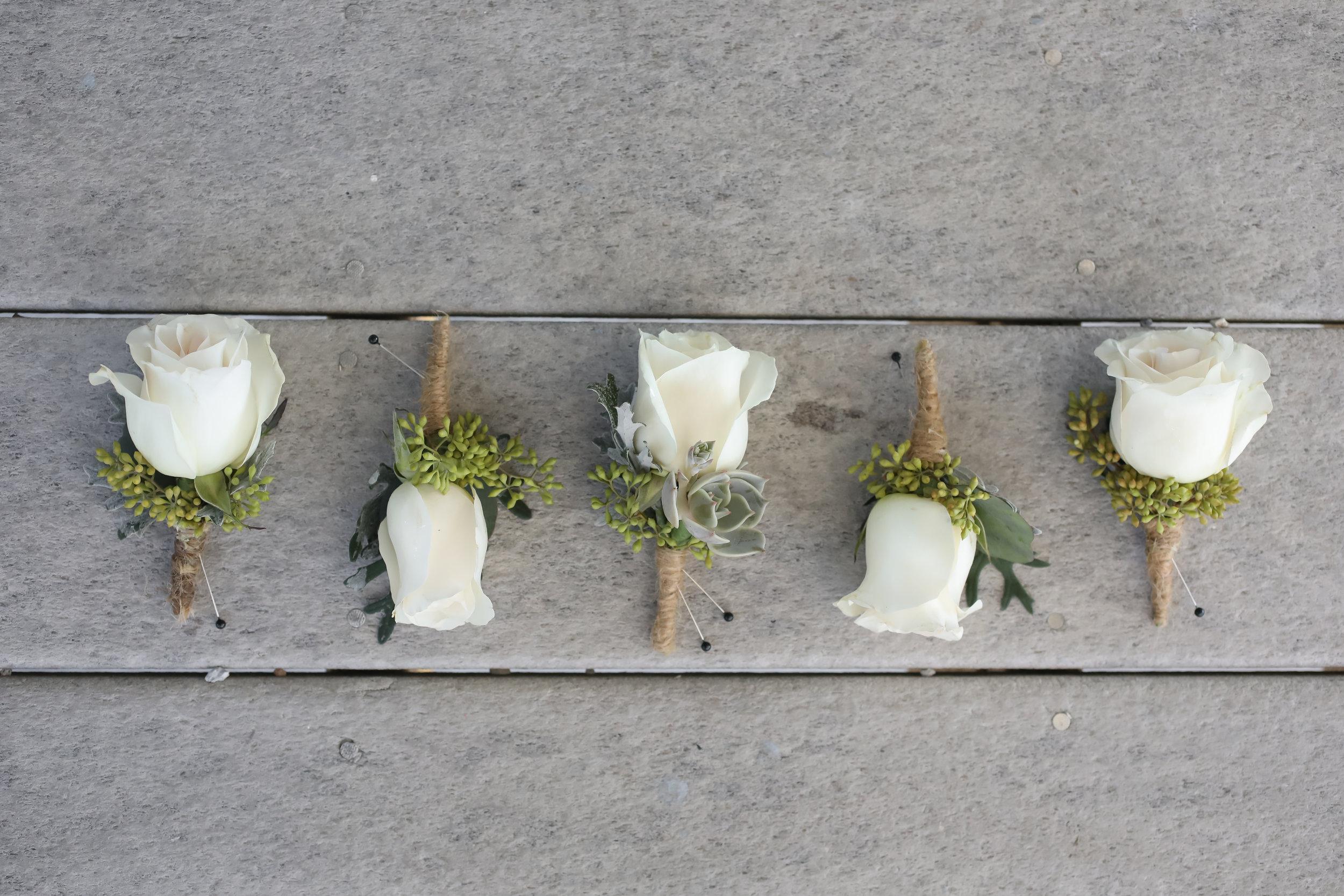 The boutonnieres reflected the clean color palette and unique succulent accents of the floral arrangements.